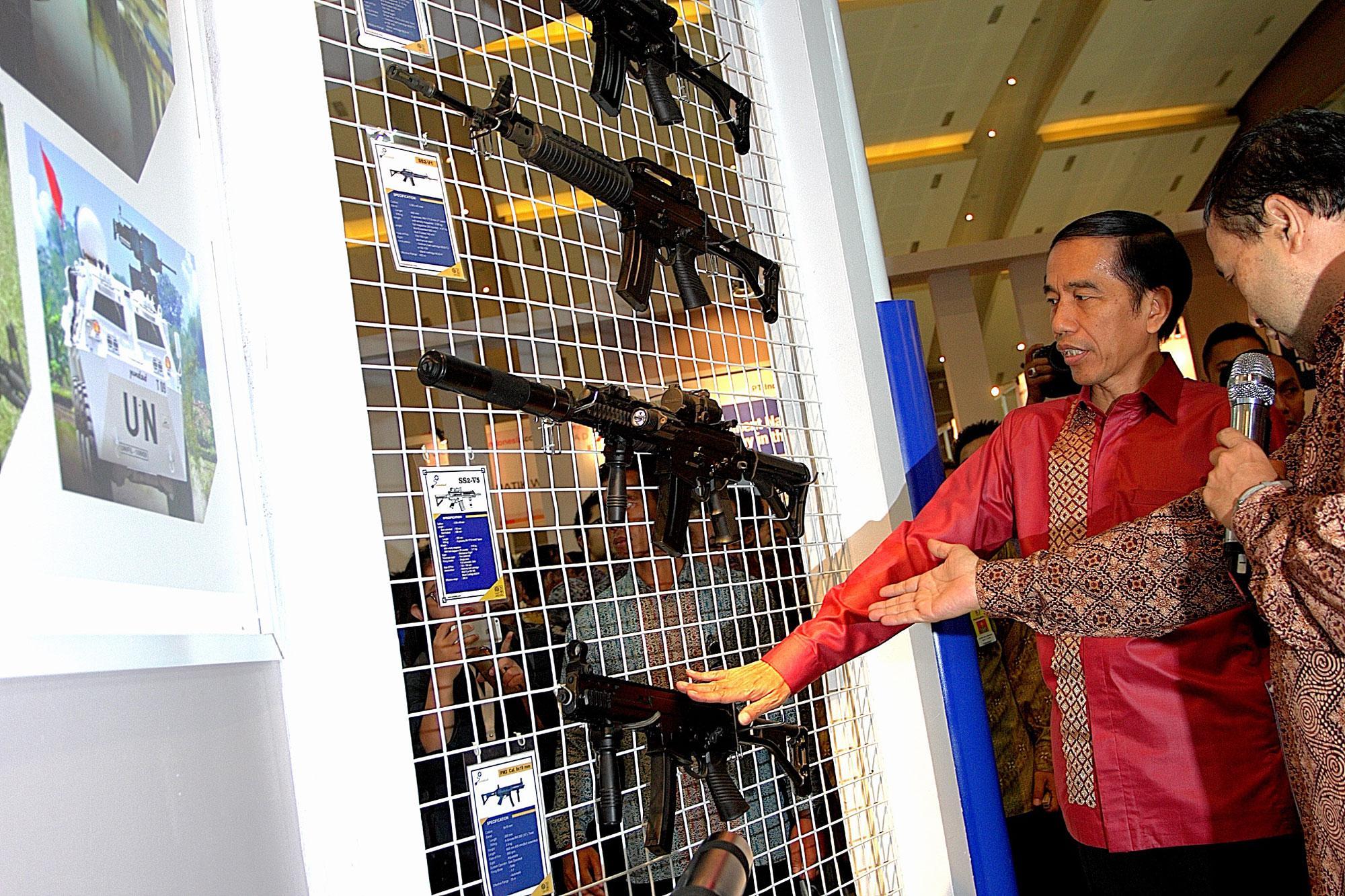 Presiden Joko Widodo mengamati senapan serbu produksi PT Pindad (Persero) ketika mengunjungi pameran Trade Expo Indonesia ke-30 Tahun 2015 di Arena Pekan Raya Jakarta, Kemayoran, Jakarta, Rabu (21/10).