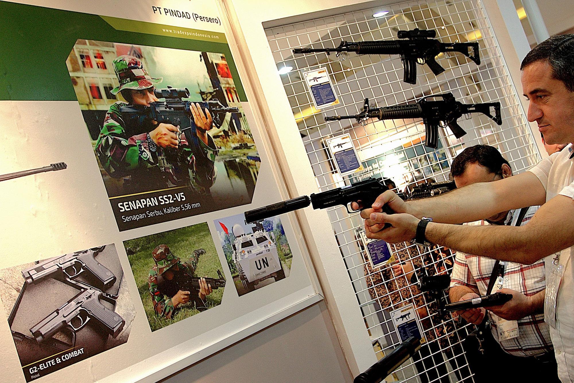 Pengunjung memperhatikan senjata produksi PT PINDAD di Trade Expo Indonesia ke-30 Tahun 2015 di Arena Pekan Raya Jakarta, Kemayoran, Jakarta, Rabu (21/10). Pameran tahunan yang menampilkan berbagai produk Indonesia berkualitas ekspor itu digelar hingga 25