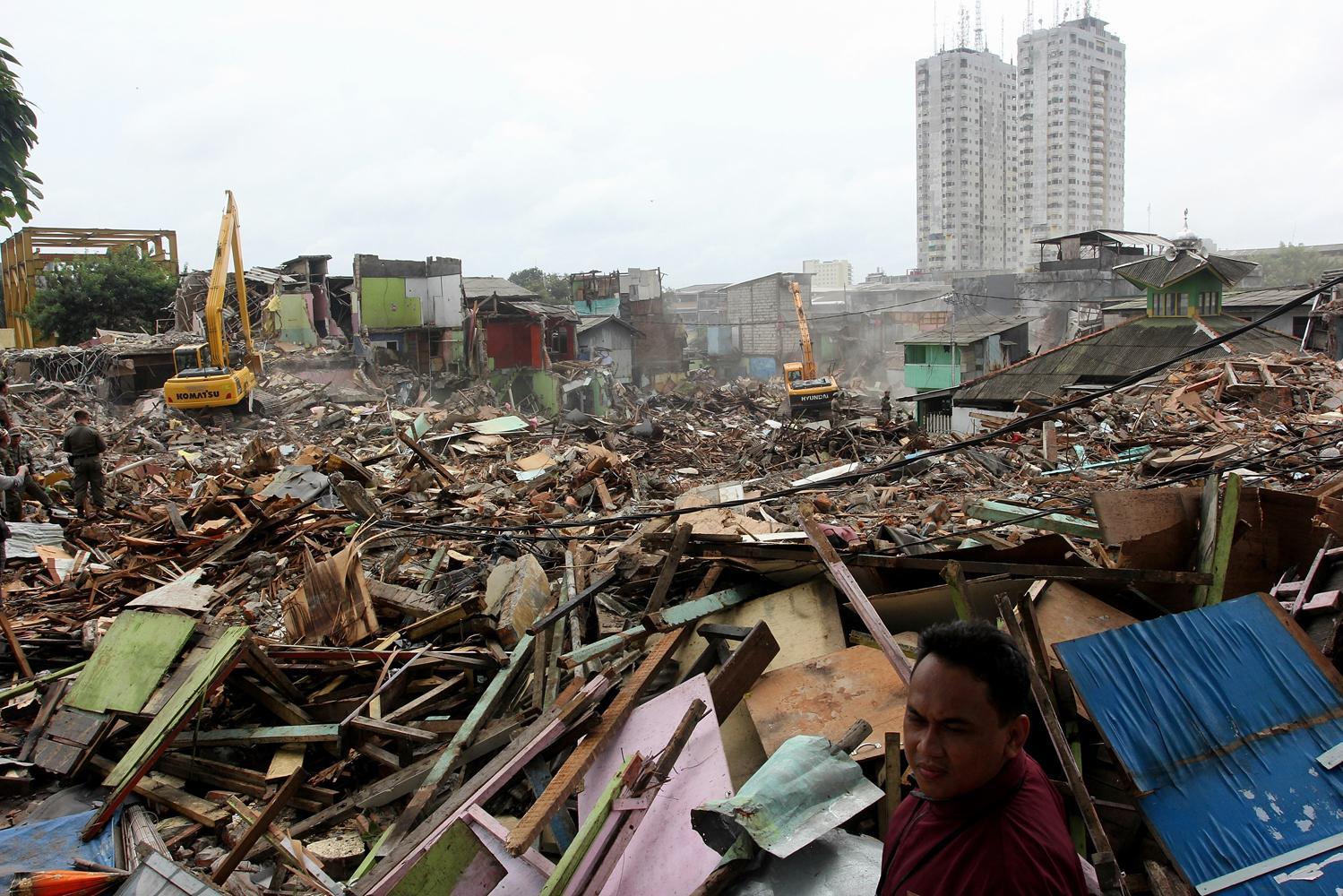 Petugas Satpol PP melihat pembongkar bangunan dengan menggunakan alat berat di kawasan Kalijodo, Jakarta, Senin (29/2). Pemprov DKI Jakarta membongkar ratusan bangunan di kawasan tersebut untuk dijadikan Ruang Terbuka Hijau (RTH).