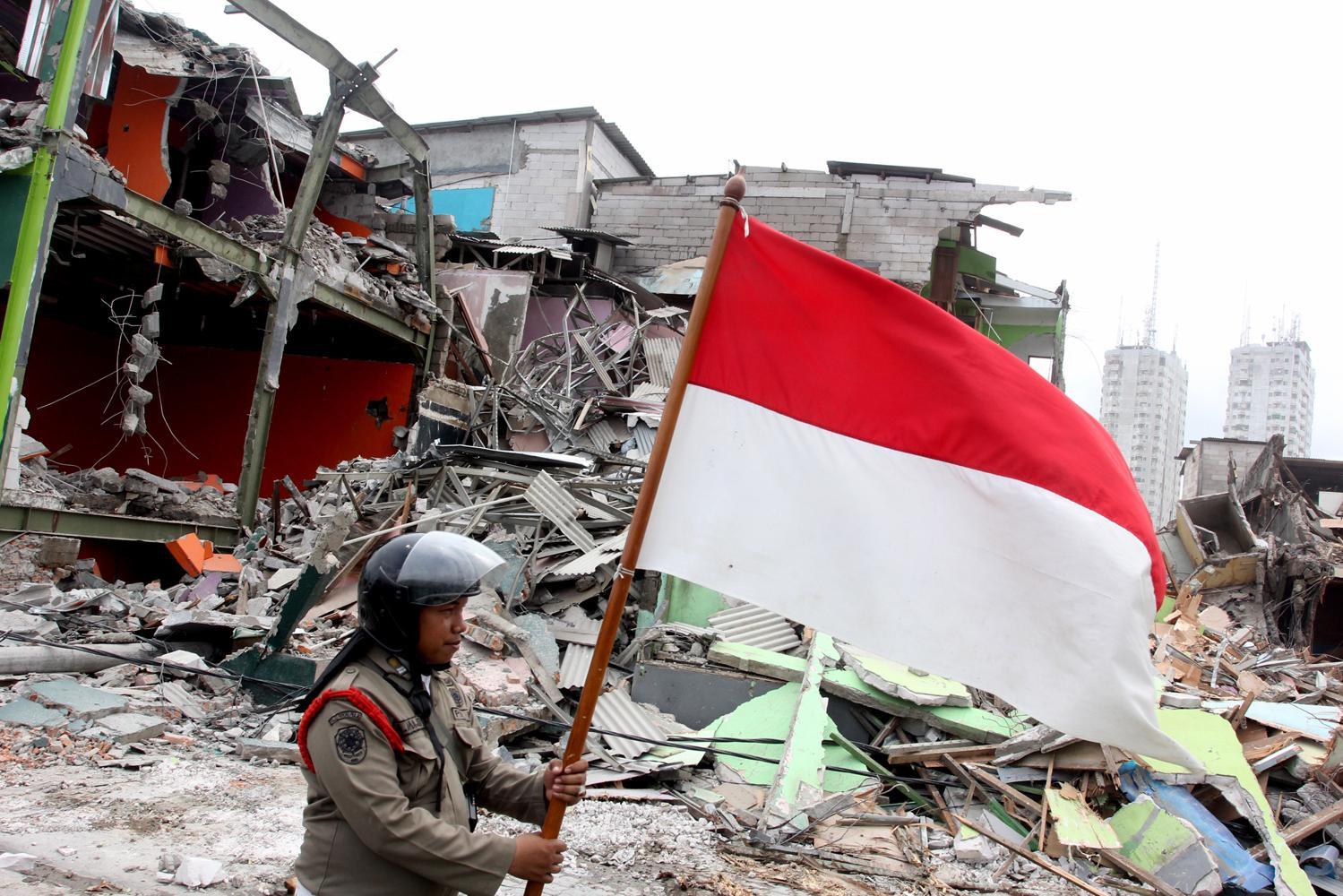 Petugas Satpol PP memindahkan bendera merah putih milik warga di kawasan Kalijodo, saat penataan bangunan , Jakarta, Senin (29/2). Pemprov DKI Jakarta membongkar ratusan bangunan di kawasan tersebut untuk dijadikan Ruang Terbuka Hijau (RTH).
