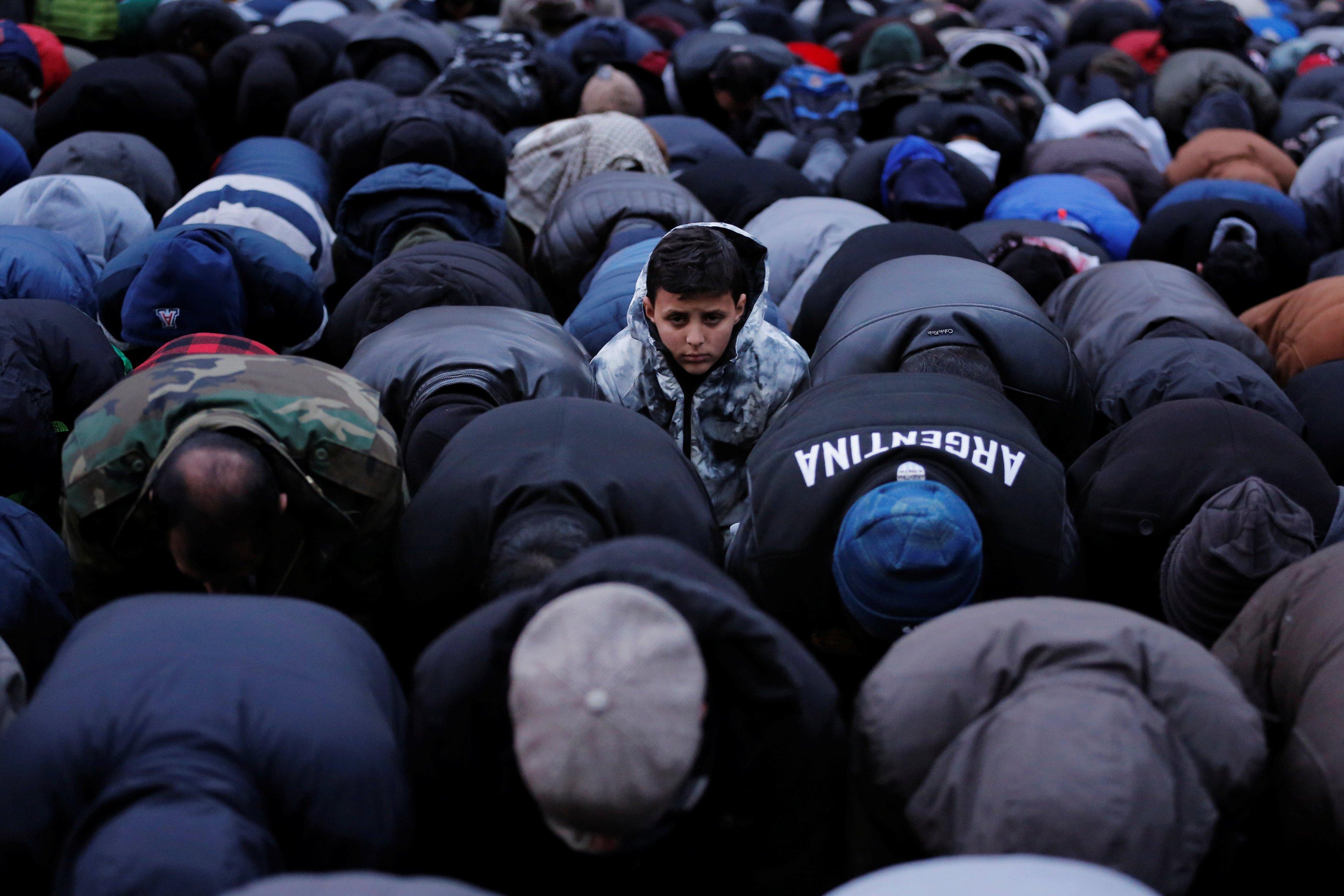 Seorang anak lelaki melihat saat para pendemo beribadah ketika berpartisipasi dalam sebuah protes oleh komunitas Yaman terhadap larangan perjalanan yang diberlakukan oleh Presiden Amerika Serikat Donald Trump di Brooklyn, New York, Amerika Serikat, Kamis (2/2).