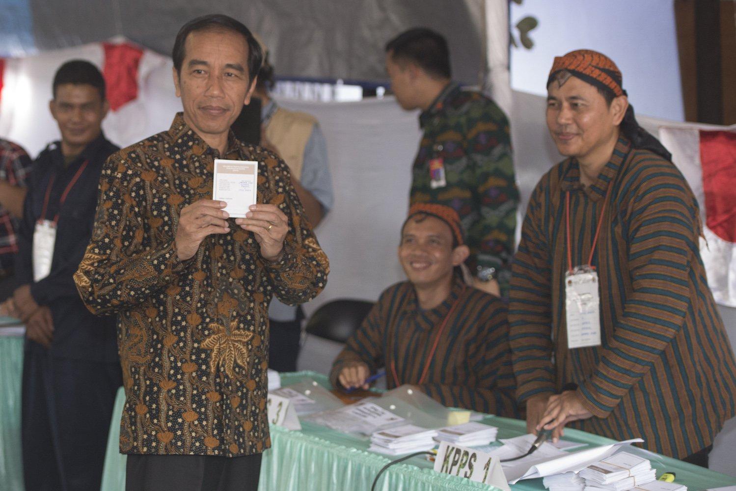 Presiden Joko Widodo (kiri) menunjukkan surat suara sebelum mencolobos dalam Pilkada DKI Jakarta di TPS 04 Gambir, Jakarta, Rabu (15/2). Komisi Pemilihan Umum (KPU) menggelar pemilihan umum kepala daerah secara serentak di 101 daerah pemilihan.