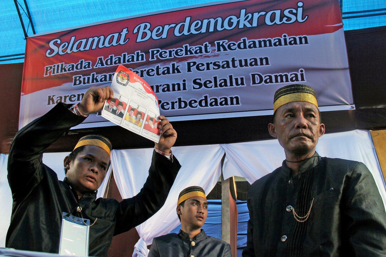 Petugas Kelompok Penyelenggara Pemungutan Suara (KPPS) pilkada gubernur menggenakan pakaian adat Mamuju saat penghitungan surat suara di TPS 29 jln Emi Sailan, Mamuju, Sulawesi Barat, Rabu (15/2). Pakaian adat tersebut digunakan sebagai daya tarik warga untuk datang ke TPS menggunakan hak pilihnya.