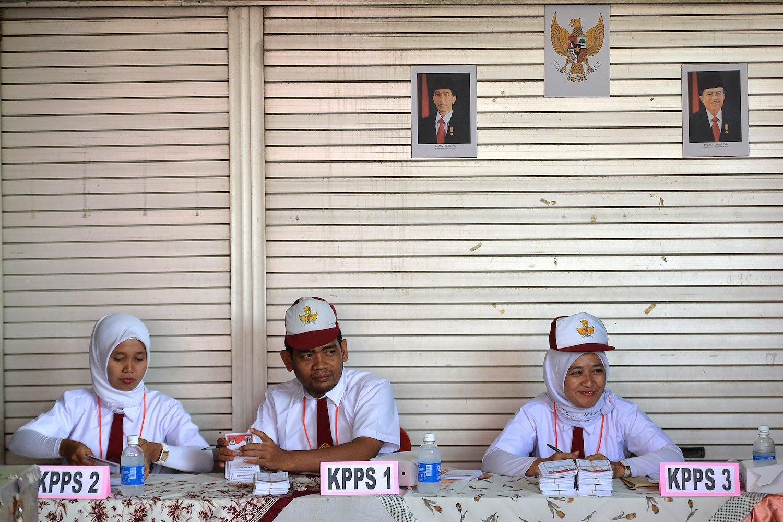 Petugas KPPS berkostum seragam pelajar sekolah dasar menyiapkan surat suara di TPS 45 Kelurahan Kebon Pala, Jakarta, Rabu (15/2). Petugas KPPS berinisiatif menggunakan kostum seragam pelajar sekolah dasar tersebut agar warga tertarik untuk mencoblos dalam Pilkada Gubernur dan Wakil Gubernur DKI Jakarta.