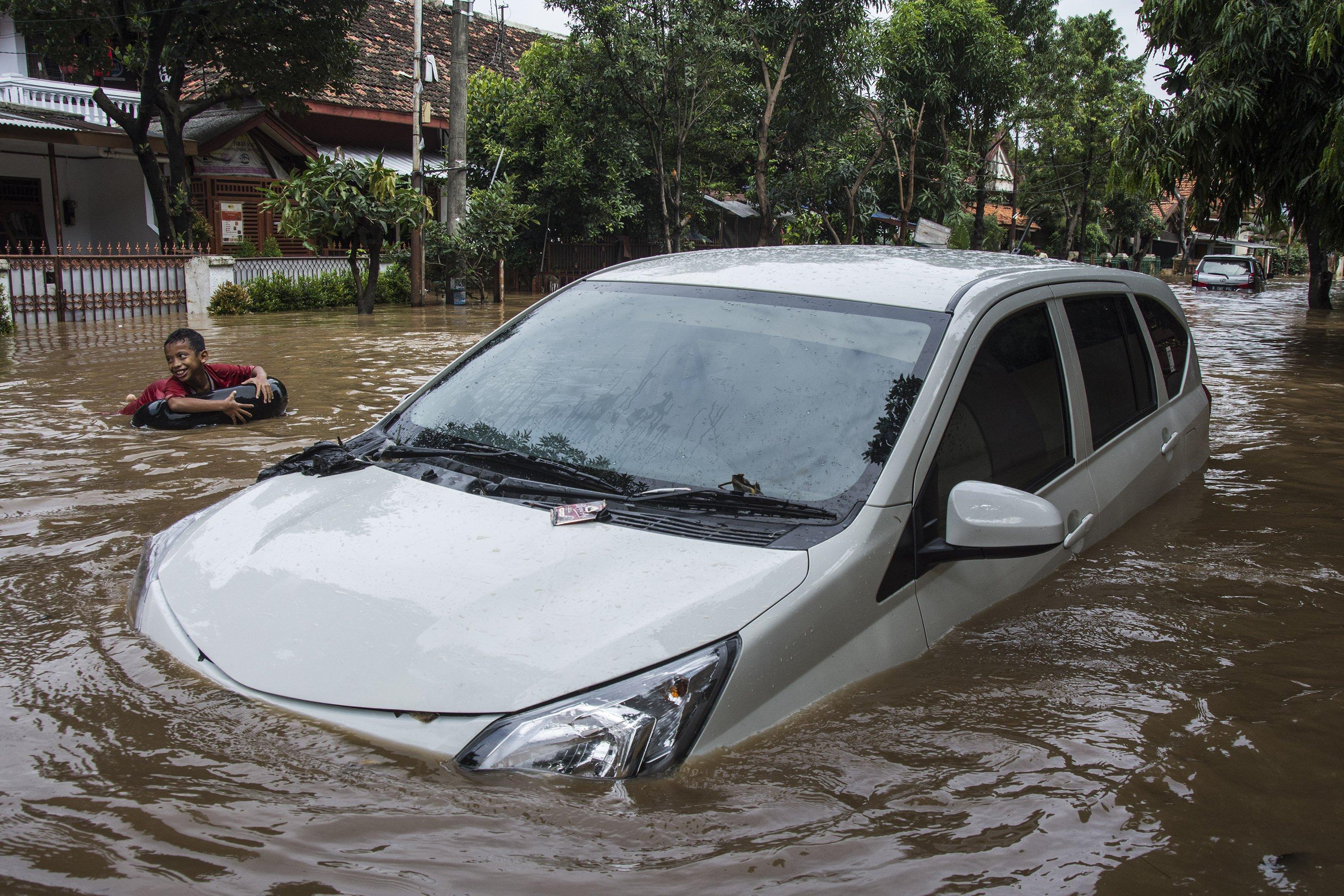Seorang anak bermain air di dekat mobil yang terendam air luapan Sungai Ciliwung di RT 001 RW 02 Kelurahan Bukitduri, Tebet Jakarta, Kamis (16/2). Banjir kiriman itu menggenangi sejumlah wilayah bantaran kali, seperti Bukit Duri, Tebet, Rawajati, Kalibata, Jatinegara, dan sejumlah wilayah lainnya dengan ketinggian genangan air bervariasi di wilayah-wilayah tersebut.
