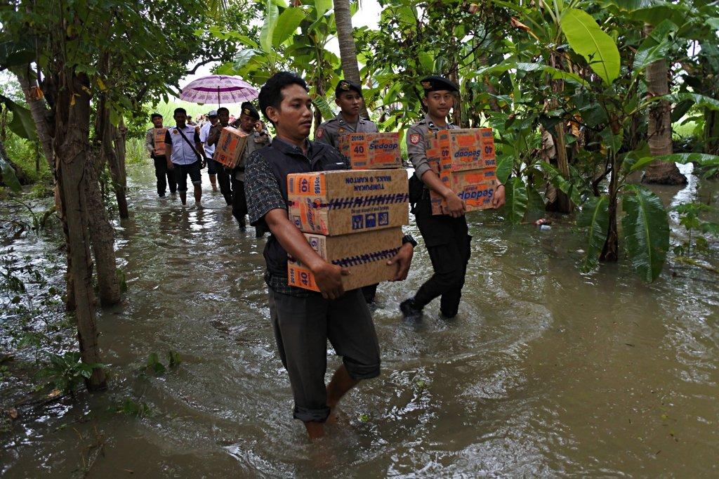 Sejumlah anggota Polres Situbondo membawa bantuan untuk korban banjir di Desa Kendit, Kendit, Situbondo, Jawa Timur, Selasa (31/1). Polres Situbondo menyalurkan bantuan berupa air minum kemasan, mie instan, obat-obatan dan pemeriksaan kesehatan gratis bagi korban banjir.