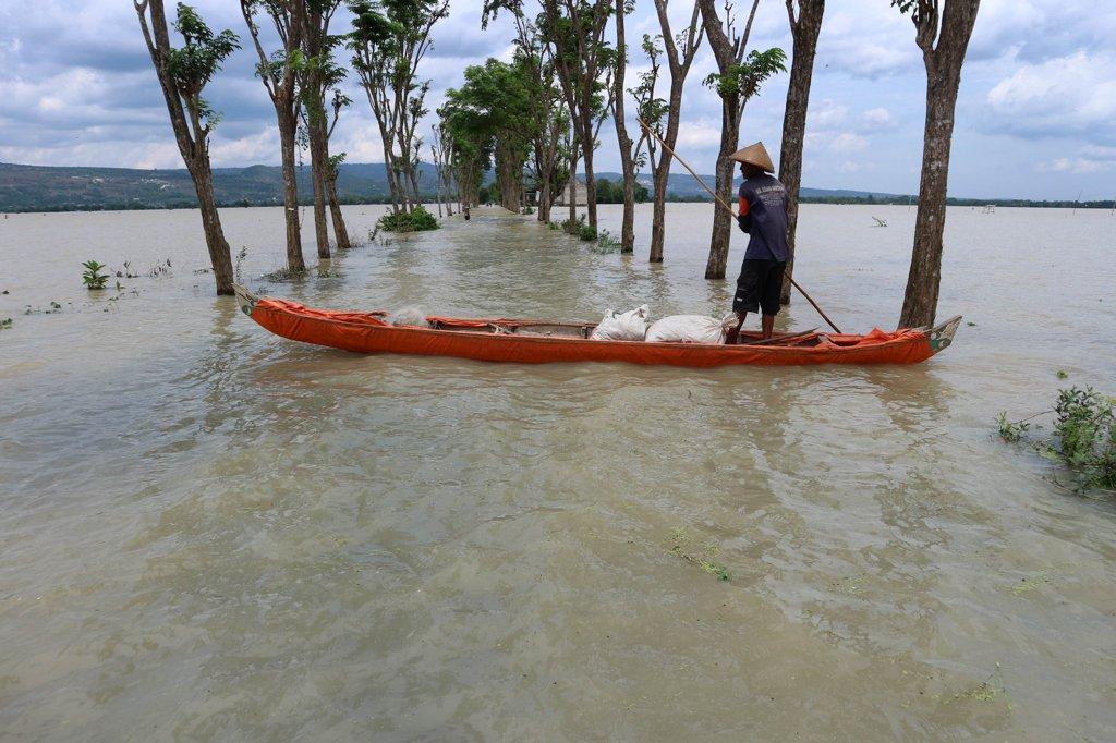Seorang warga dengan perahu menyeberang jalan yang terendam banjir luapan Bengawan Solo di Desa Kanorejo, Kecamatan Rengel, Kabupaten Tuban, Jawa Timur, Minggu (5/2). Warga di Kecamatan Rengel dan Tuban, terpaksa beralih bekerja mencari ikan karena beberapa kali menanam tanaman padi selalu rusak terendam banjir.