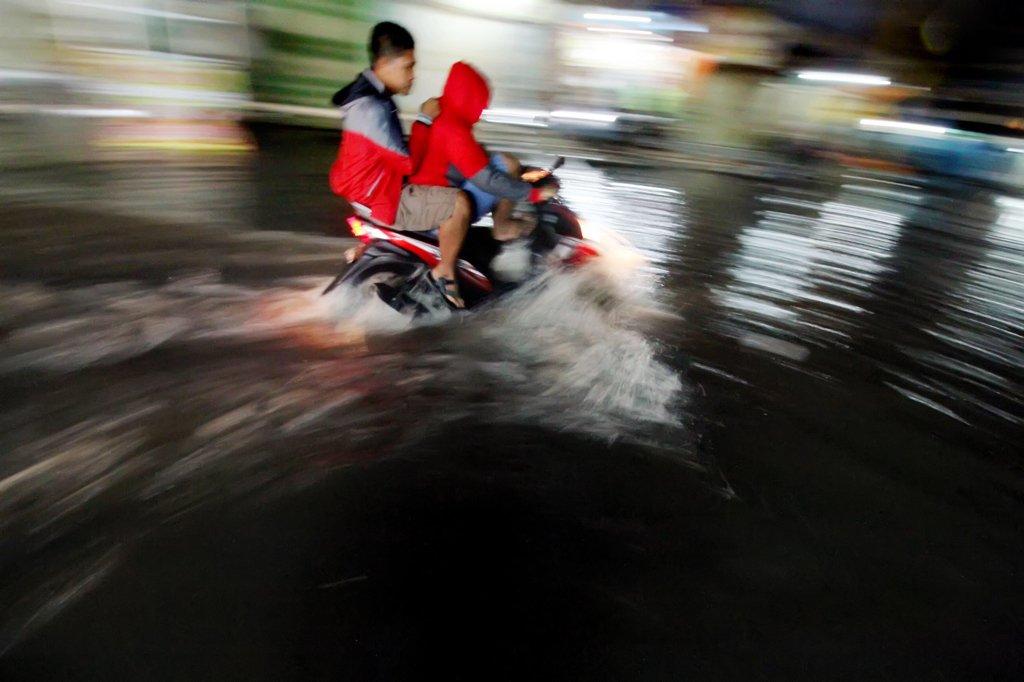 Pengendara sepeda motor berusaha menerobos genangan air saat banjir pasca hujan deras di jalan Sukaramai Kota Lhokseumawe, Provinsi Aceh, Senin (23/1) malam. Warga meminta kepada Pemerintah setempat melakukan perbaikan drainase kota agar tidak selalu kebanjiran saat terjadi hujan yang mengakibatkan pusat kota lumpuh dan mengganggu aktivitas warga.
