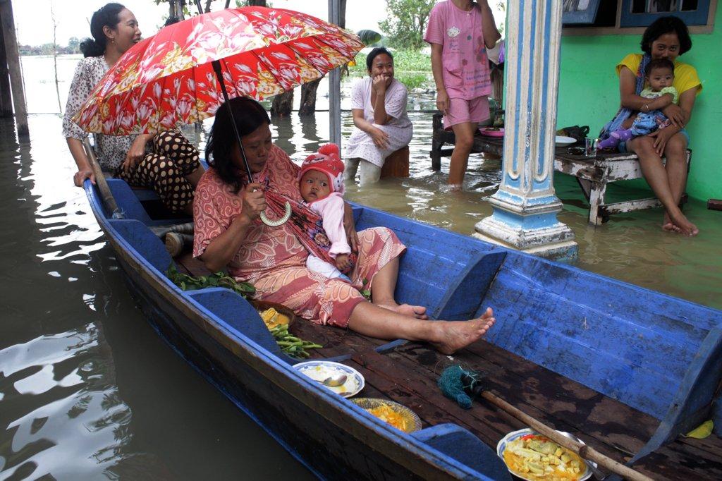 Warga menggunakan perahu untuk beraktivitas di rumah yang terendam banjir di desa Kedungringin, Beji, Pasuruan, Jawa Timur, Kamis (2/2). Hujan yang turun dengan intensitas cukup tinggi beberapa hari terakhir merendam ratusan rumah di lima desa kecamatan beji, Pasuruan dengan ketinggian 40-60 cm sehingga menyebabkan aktivitas masyarakat terganggu. \n