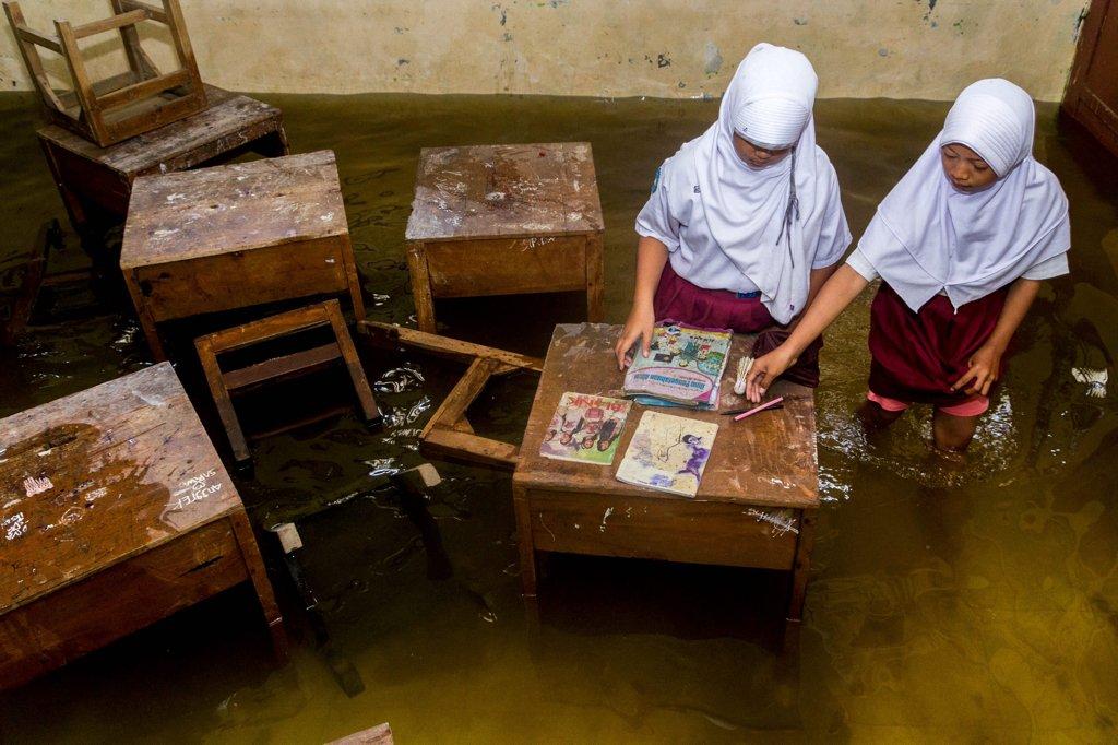 Siswa menyelamatkan buku yang terendam banjir di ruang kelas di SD Negeri Sayung 1 Demak, Jawa Tengah, Senin (20/2). Meski banjir berangsur surut namun sejumlah ruang kelas di sekolah itu masih tergenang air. Untuk sementara kegiatan belajar mengajar dipindahkan ke ruang yang sudah tidak terendam. \n