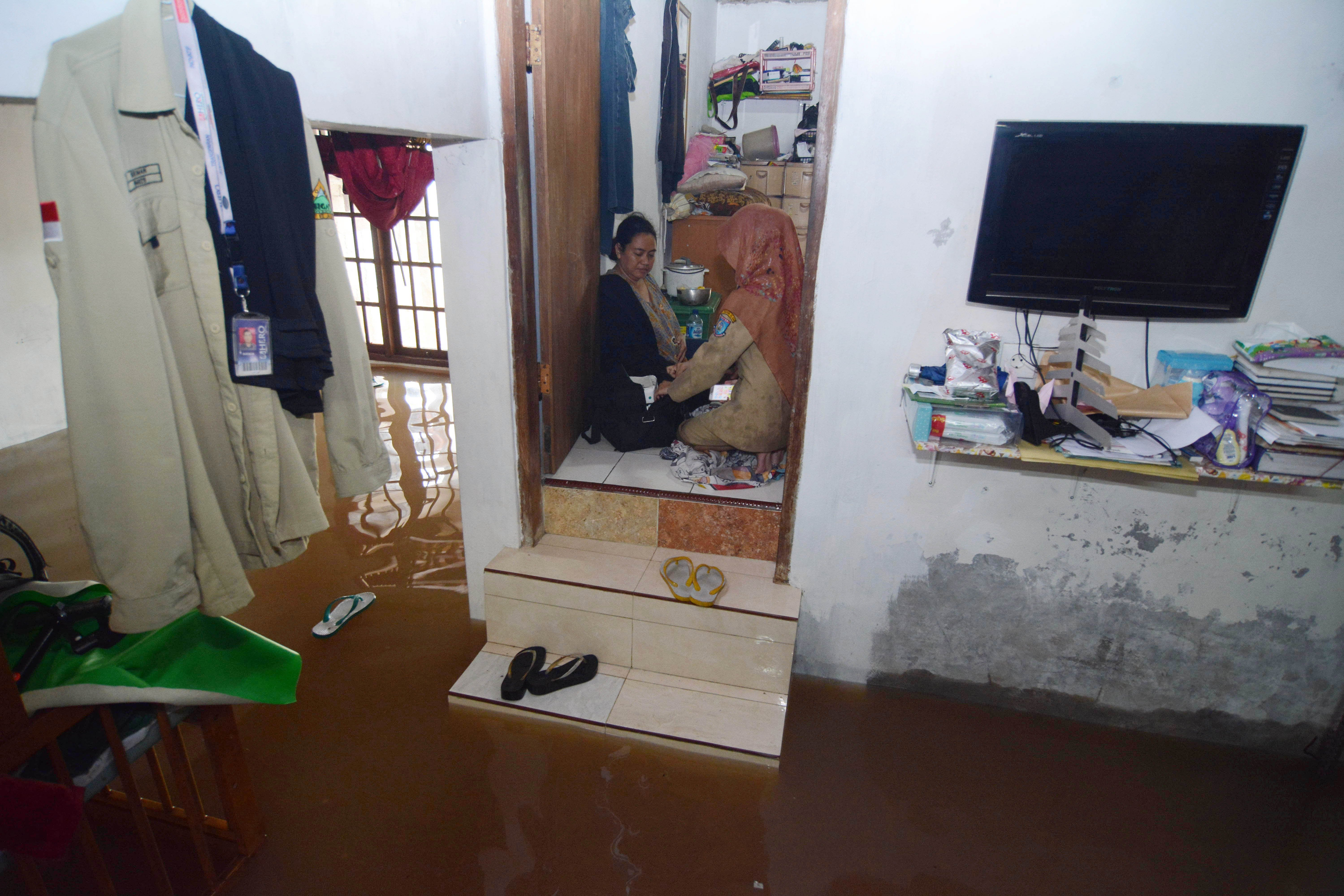 Petugas Puskesmas memeriksa warga yang sakit saat banjir melanda kawasan Perumahan Kampung Bulak, Pondok Aren, Kota Tangerang Selatan, Banten, Selasa (21/2). Meluapnya anak Kali Angke menyebabkan ratusan rumah di Pondok Aren terendam hingga setinggi 70 cm.