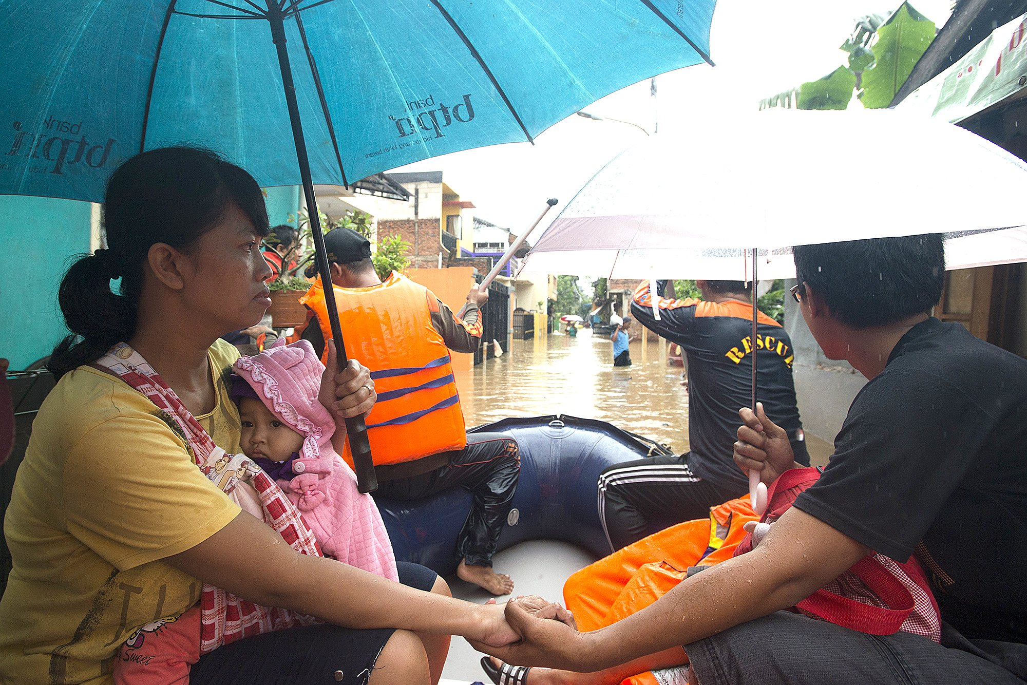 Warga menggunakan perahu untuk menuju rumahnya yang terendam banjir di Kelurahan Cipinang Melayu, Kecamatan Makassar, Jakarta, Senin (20/2). Banjir yang terjadi di kawasan tersebut akibat luapan dari Kali Sunter.