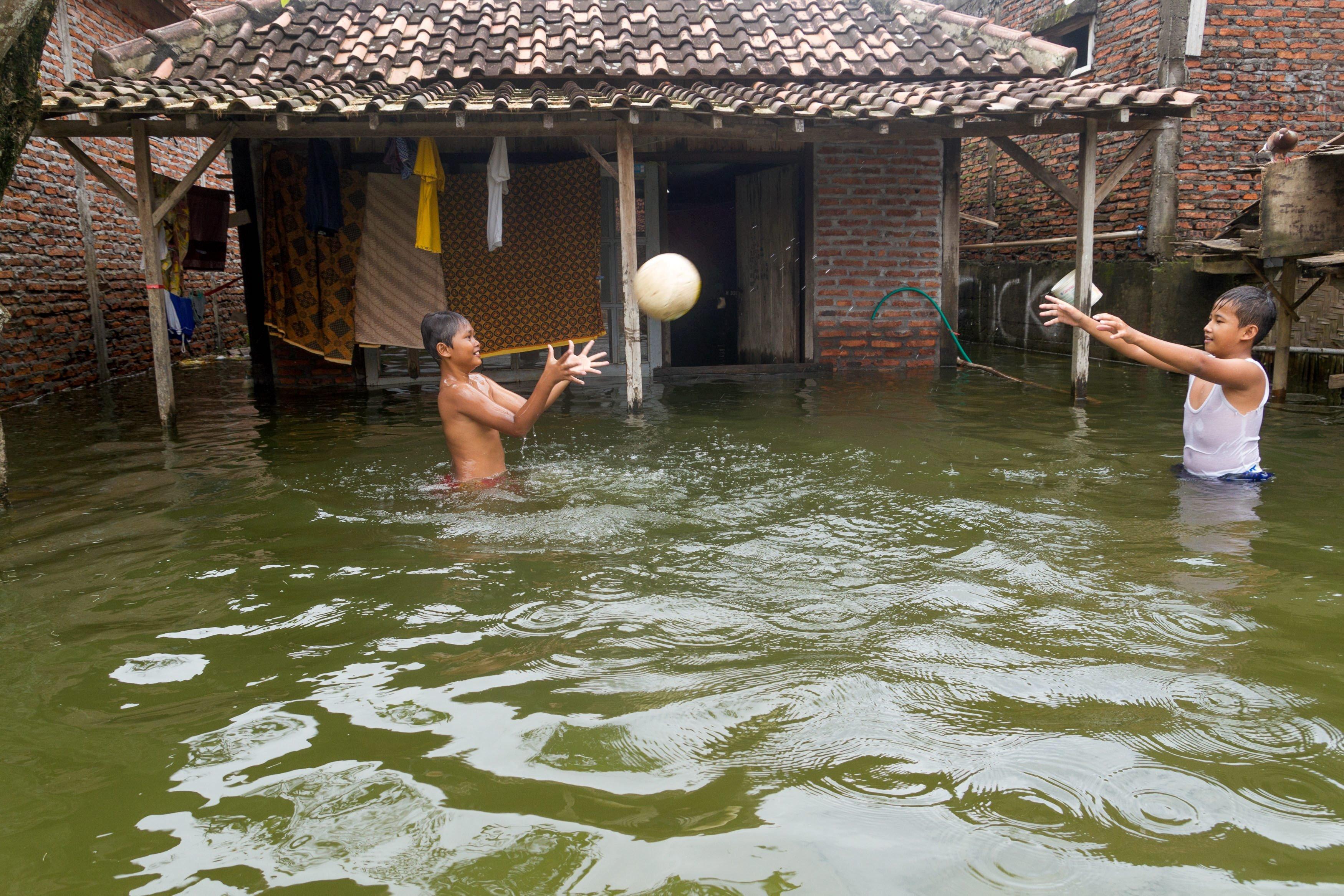 Dua anak bermain di depan rumahnya yang terendam banjir di Sayung, Demak, Jawa Tengah. Banjir yang disebabkan luapan Sungai Dombo yang tak mampu menampung debit air akibat tingginya intensitas hujan tersebut merendam sekitar 1.450 rumah warga dengan ketinggian air 30 cm-1 meter.