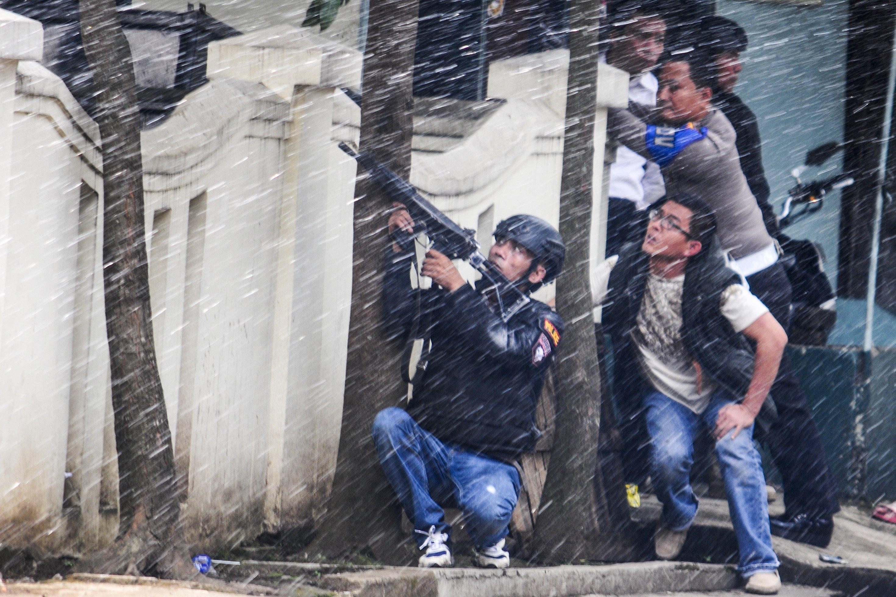 Petugas kepolisian bersenjata lengkap berusaha melumpuhkan terduga teroris di Kantor Kelurahan Arjuna, Bandung, Jawa Barat, Senin (27/2).