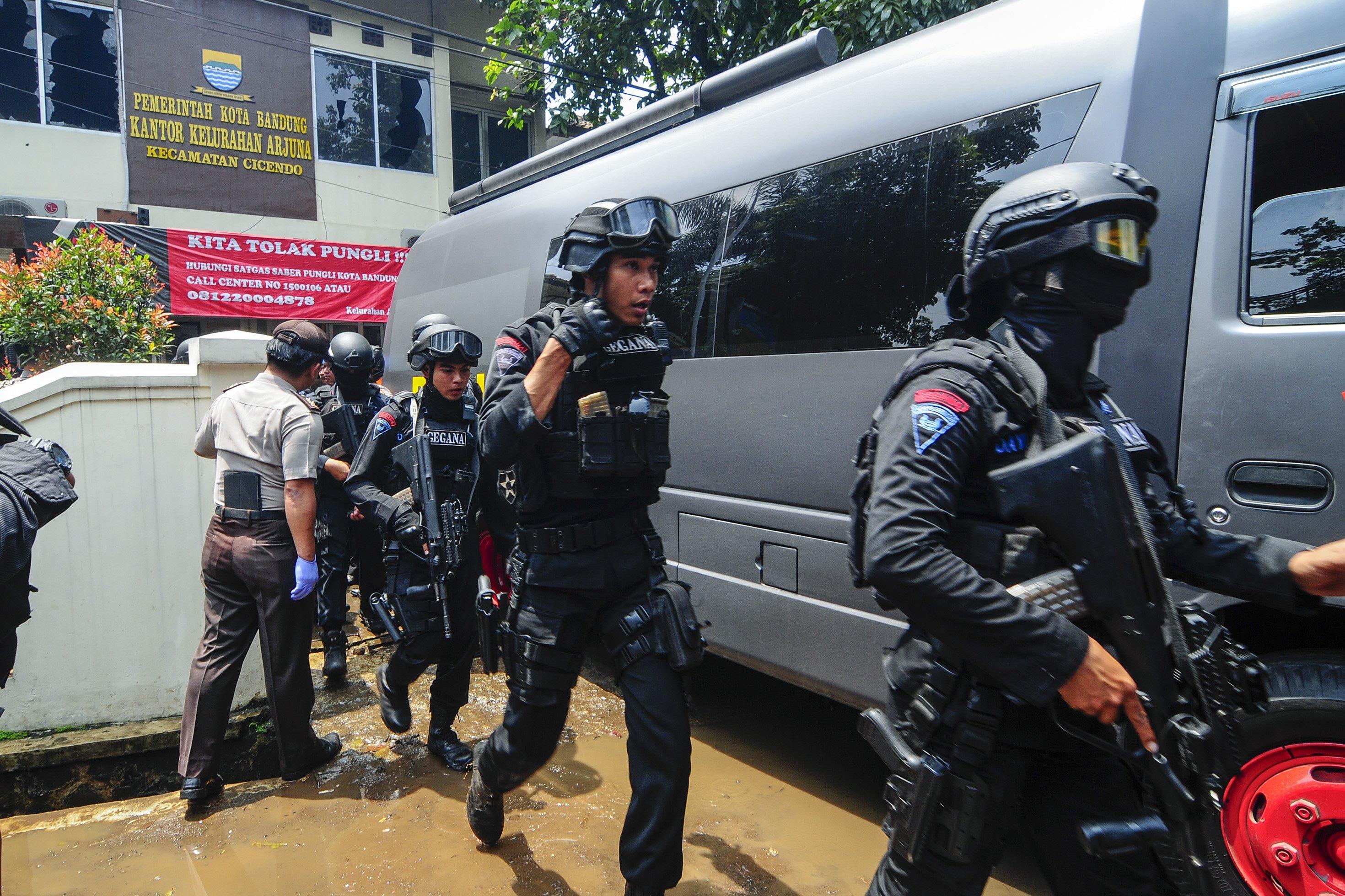 Petugas kepolisian bersenjata lengkap bergegas keluar seusai berhasil menangkap terduga teroris di Kantor Kelurahan Arjuna, Bandung, Jawa Barat, Senin (27/2).