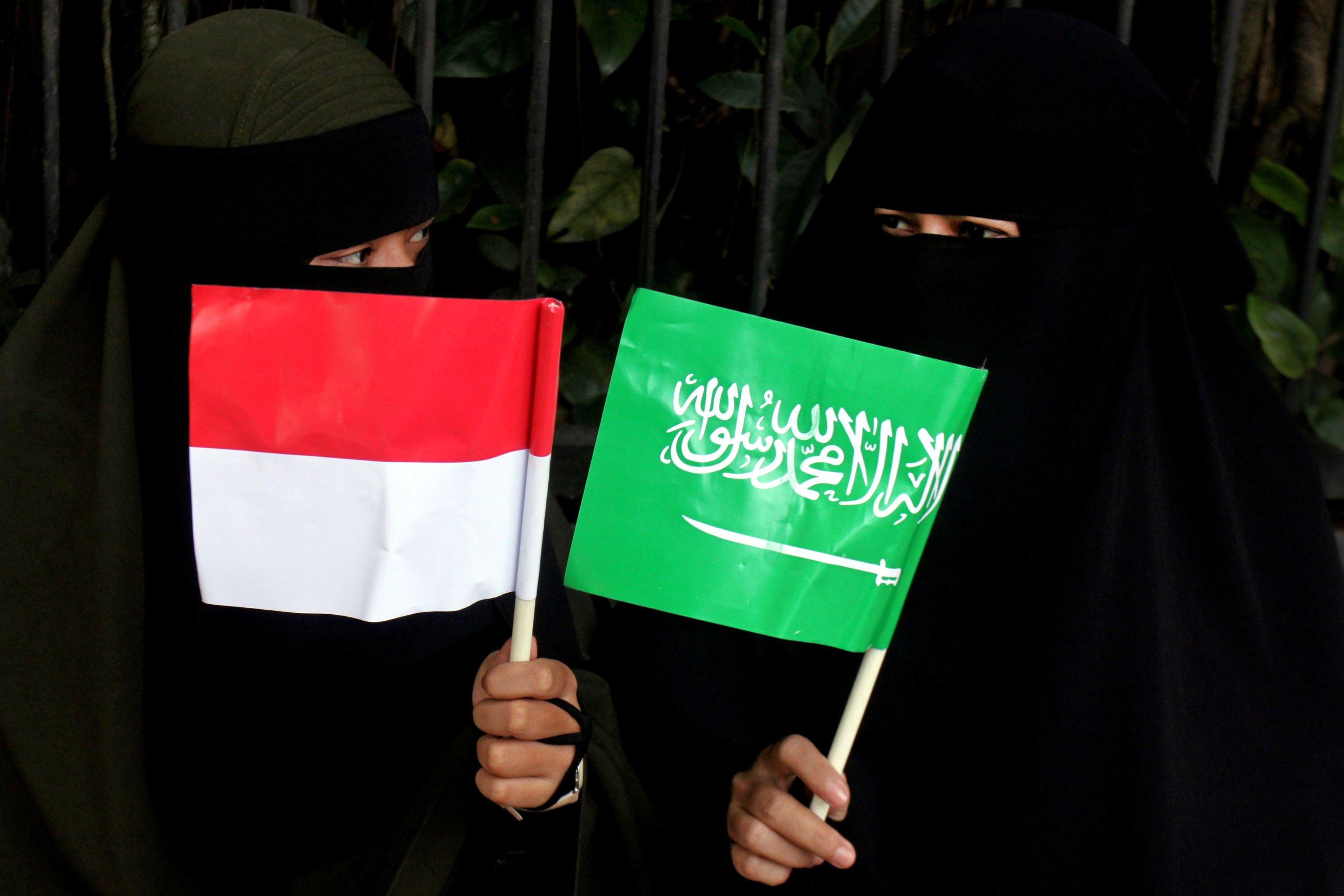 Dua orang warga memegang bendera untuk menyambut kedatangan Raja Salman di sekitar Istana Bogor, Kota Bogor, Jawa Barat, Rabu (1/3). Warga Bogor antusias menyambut kedatangan Raja Arab Saudi, Salman bin Abdulaziz al-Saud dalam kunjungannya ke Istana Bogor.