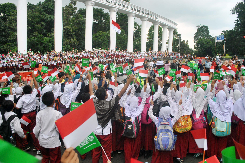Ribuan pelajar Kota Bogor mengibarkan bendera Merah Putih dan Arab Saudi saat kedatangan Raja Salman di Tepas Lawang Salapan, jalan Otista, Kota Bogor, Jawa Barat, Rabu (1/3). Raja Salman bersama delegasi Arab Saudi tiba di Istana Kepresidenan Bogor untuk membicarakan kerjasama bilateral antara dua negara.