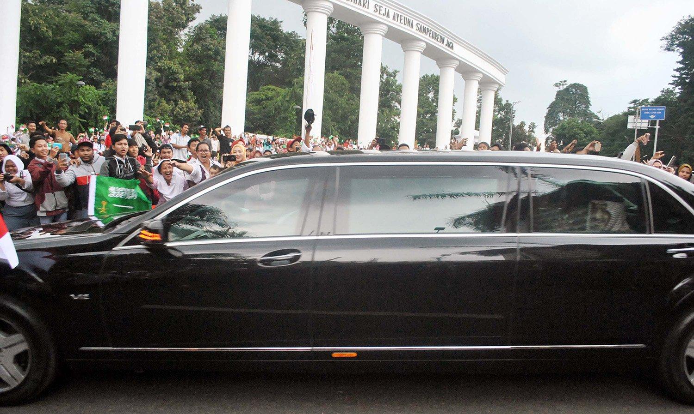 Raja Salman (kanan) tersenyum dari balik jendela mobilnya melihat pelajar dan warga Bogor menyambut kedatangannya di Tepas Lawang Salapan, jalan Otista, Kota Bogor, Jawa Barat, Rabu (1/3). Raja Salman bersama delegasi Arab Saudi tiba di Istana Kepresidenan Bogor untuk membicarakan kerjasama bilateral antara dua negara.