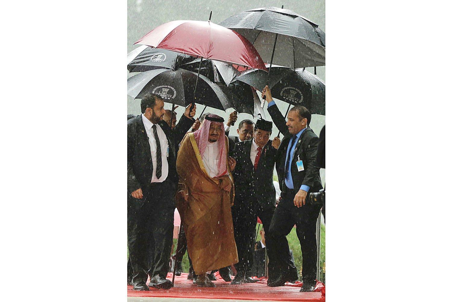 Presiden Joko Widodo (kedua kanan) dan Raja Arab Saudi Salman bin Abdulaziz Al-Saud (kedua kiri) berjalan di bawah payung saat turun hujan lebat di Istana Kepresidenan, Bogor, Jawa Barat, Rabu (1/3).