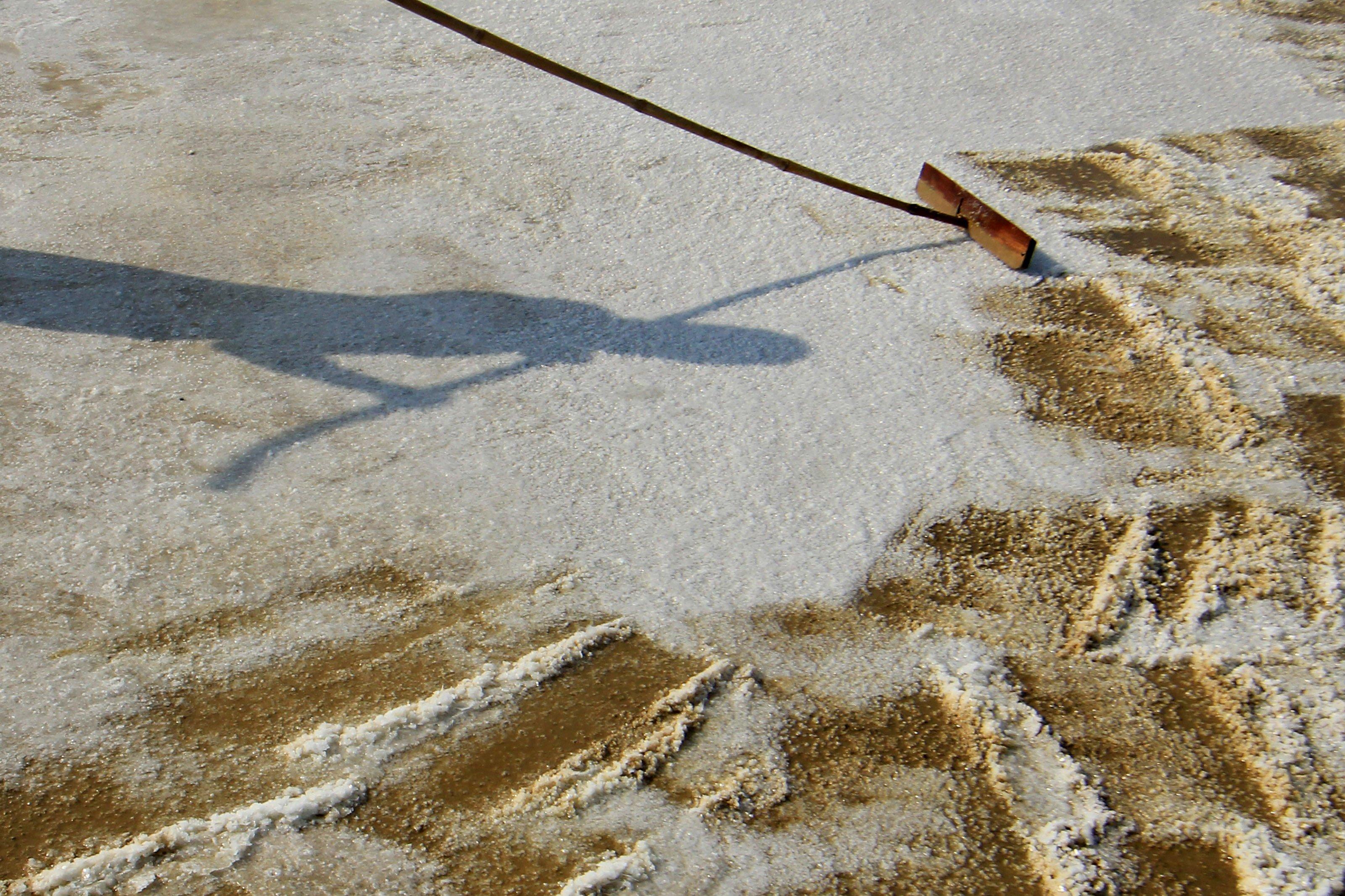 Setelah air mengering dan berubah jadi kristal berwarna putih, barulah petani memanen garam untuk dijual.