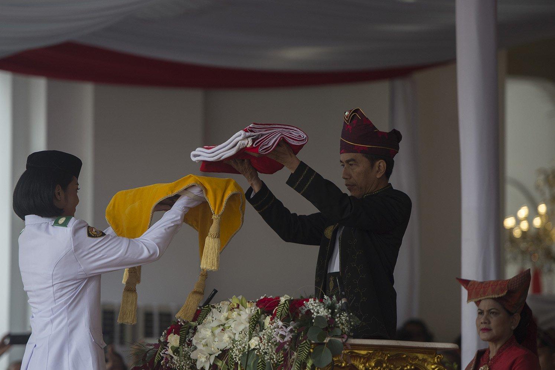 Presiden Joko Widodo (kanan) menyerahkan duplikat Sang Saka Merah Putih kepada Pembawa Bendera Merah Putih Fariza Putri Salsabila (kiri) disaksikan Ibu Negara Iriana Joko Widodo (kanan) dalam upacara peringatan detik-detik proklamasi kemerdekaan RI di Istana Merdeka, Jakarta, Kamis (17/8). HUT ke-72 RI mengambil tema Indonesia Kerja Bersama.