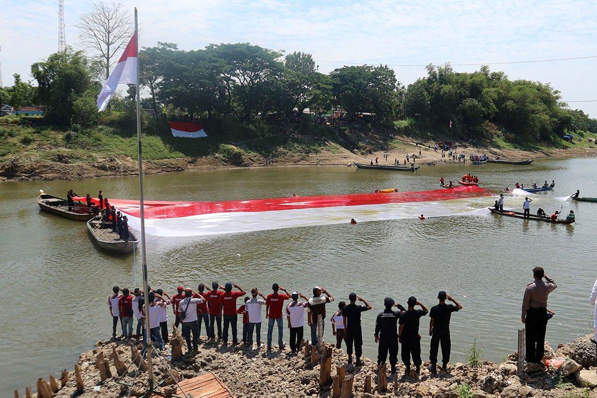 Sejumlah warga mengibarkan bendera panjang 45 meter selebar 17 meter di perairan Bengawan Solo di Bojonegoro, Jawa Timur, Kamis (17/8). Untuk membentangkan bendera di air dilakukan delapan perenang dengan bantuan warga usai upacara HUT ke-72 RI yang digelar warga dua desa di bantaran Bengawan Solo.