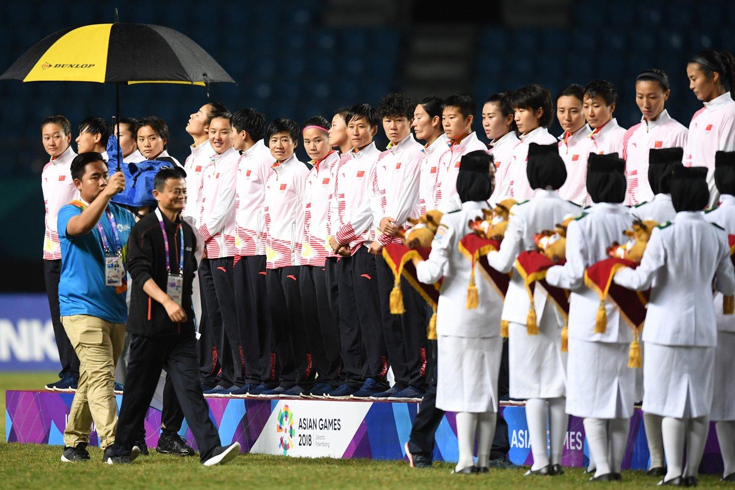 Executive Chairman Alibaba Group Jack Ma (kedua kiri) berjalan menuju podium untuk memberi boneka maskot Asian Games 2018 pada tim sepak bola wanita Cina saat pemberian medali kejuaraan sepak bola wanita Asian Games 2018 di Stadion Gelora Sriwijaya Jakabaring, Palembang, Sumatera Selatan, Jumat (31/8). Jepang menang atas Cina dengan skor 1-0 dan memastikan Jepang merah medali emas disusul Cina dengan medali perak dan Korea Selatan medali perungu.