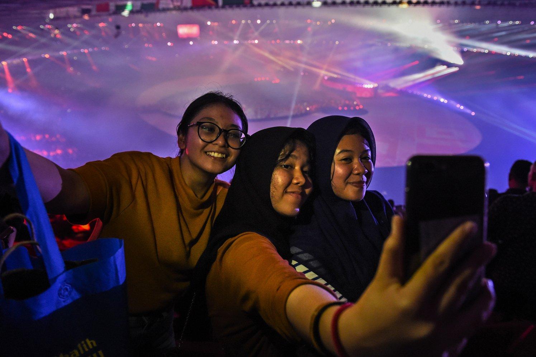 Penonton berswafoto dengan latar belakang Upacara Penutupan Asian Games ke 18, tahun 2018 di Stadion Utama Gelora Bung Karno, Senayan, Jakarta, Minggu (2/9).