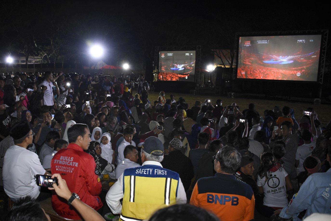 Presiden Joko Widodo (ketiga kiri) didampingi Gubernur NTB TGB Zainul Majdi (kedua kiri) bersama warga korban gempa nonton bareng upacara penutupan Asian Games 2018 di Lapangan Kecamatan Gunungsari, Lombok Barat, NTB, Minggu (2/9). Presiden Jokowi disela kunjungannya ke lokasi gempa menyempatkan diri untuk nonton bareng warga korban gempa upacara penutupan Asian Games 2018.