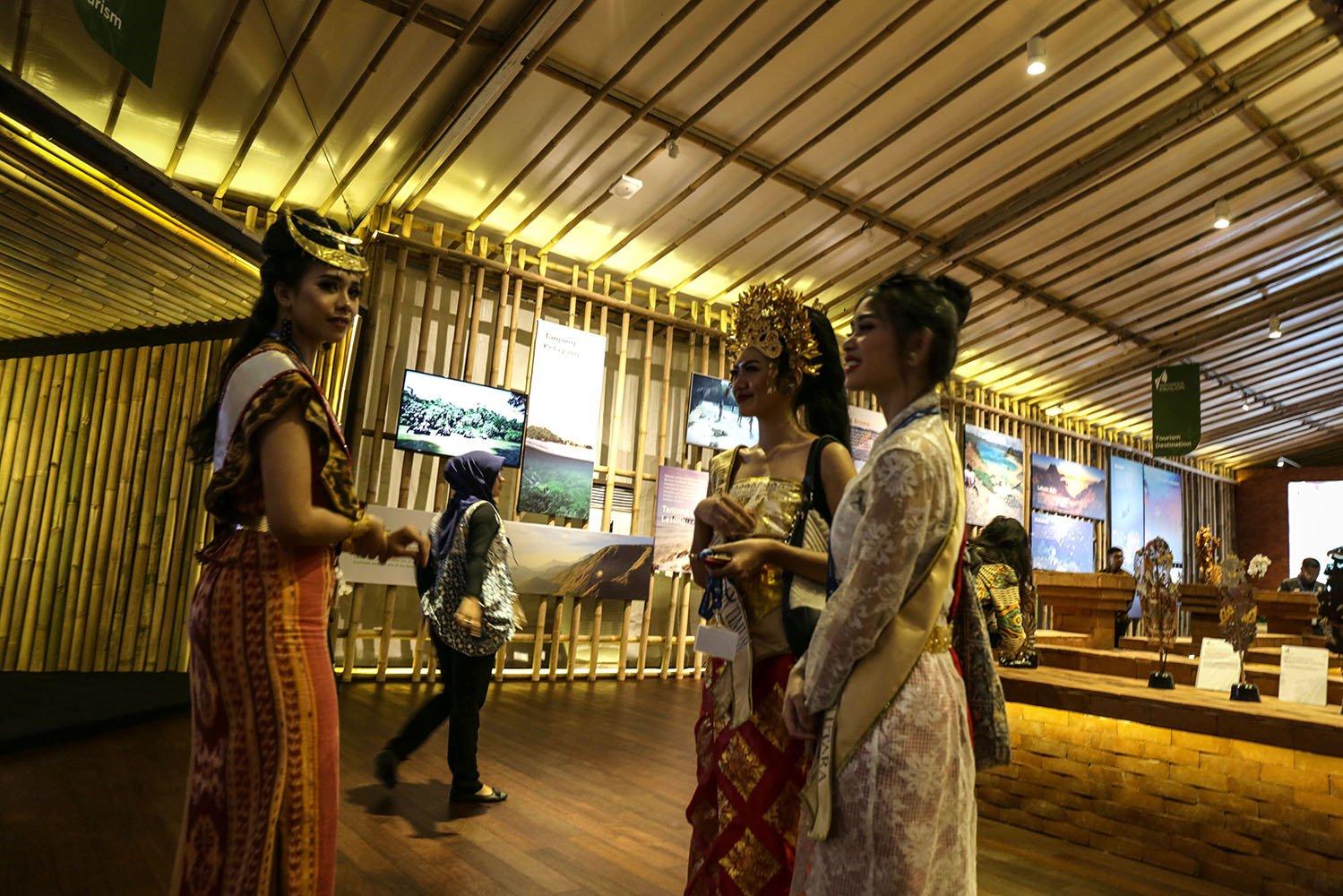 Tiga wanita pemandu Indonesia Pavilion sedang berbincang dalam pameran Indonesia Pavillion, NUsa Dua, Bali (9/10)