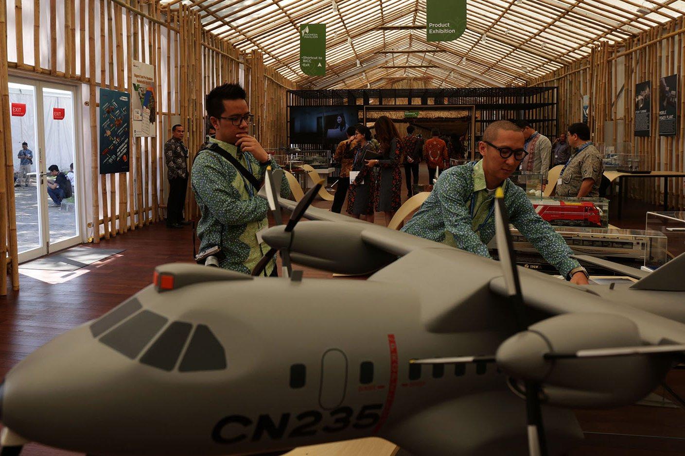 Sejumlah pengunjung menyaksikan pameran replika pesawat CN 235 produksi PT DI, di dalam acara Indonesia Pavilion 2018, Nusa Dua, Bali (12/10).
