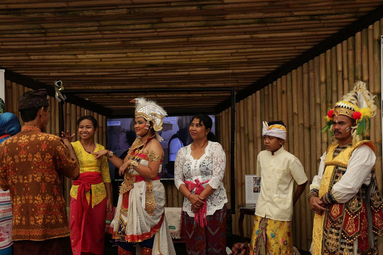 Sejumlah panitia penyelenggara berpakaian ada khas Bali berdiri di depan sebuah stand dalam acara Indoensia Pavilion , Nusa Dua Bali (12/10).