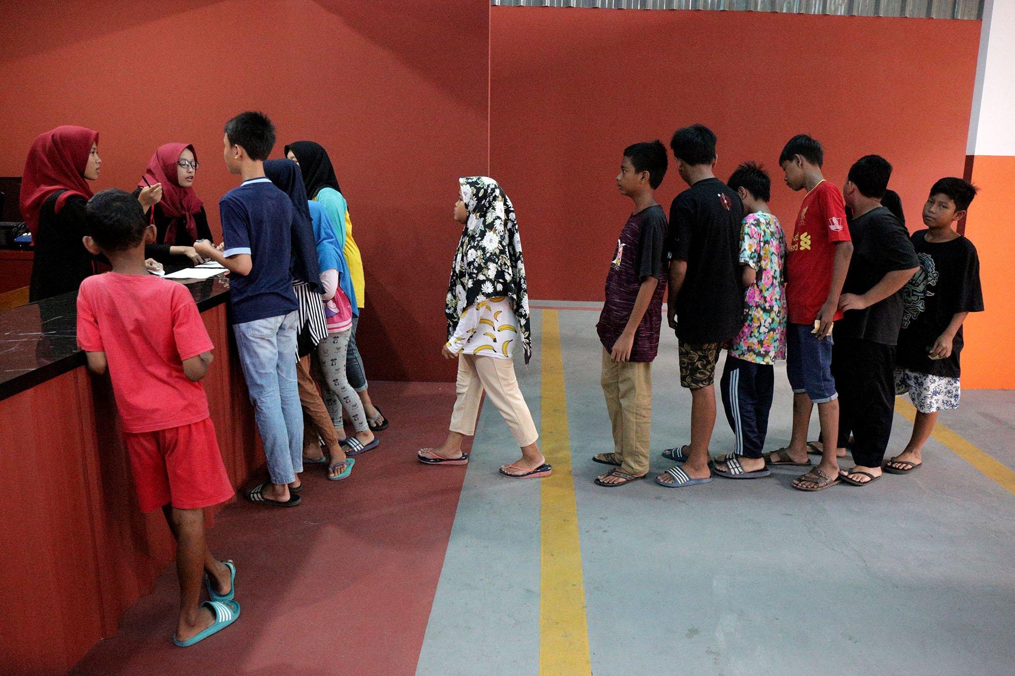 Sejumlah anak mengantre tiket untuk menonton film yang diputar di Indiskop atau Bioskop Rakyat yang di dalam Pasar Jaya Teluk Gong, Penjaringan, Jakarta Utara, Selasa (2/7/2019). Bioskop rakyat yang khusus menayangkan film-film Indonesia ini memiliki 2 studio dengan kapasitas masing-masing 128 kursi penonton, 6 speaker, 1 proyektor layar, dan 3 pendingin ruangan. Dalam masa uji coba ini, warga yang ingin menjajal bioskop rakyat ini cukup merogoh kocek Rp. 15.000 untuk dewasa dan Rp. 5.000 untuk anak kecil.