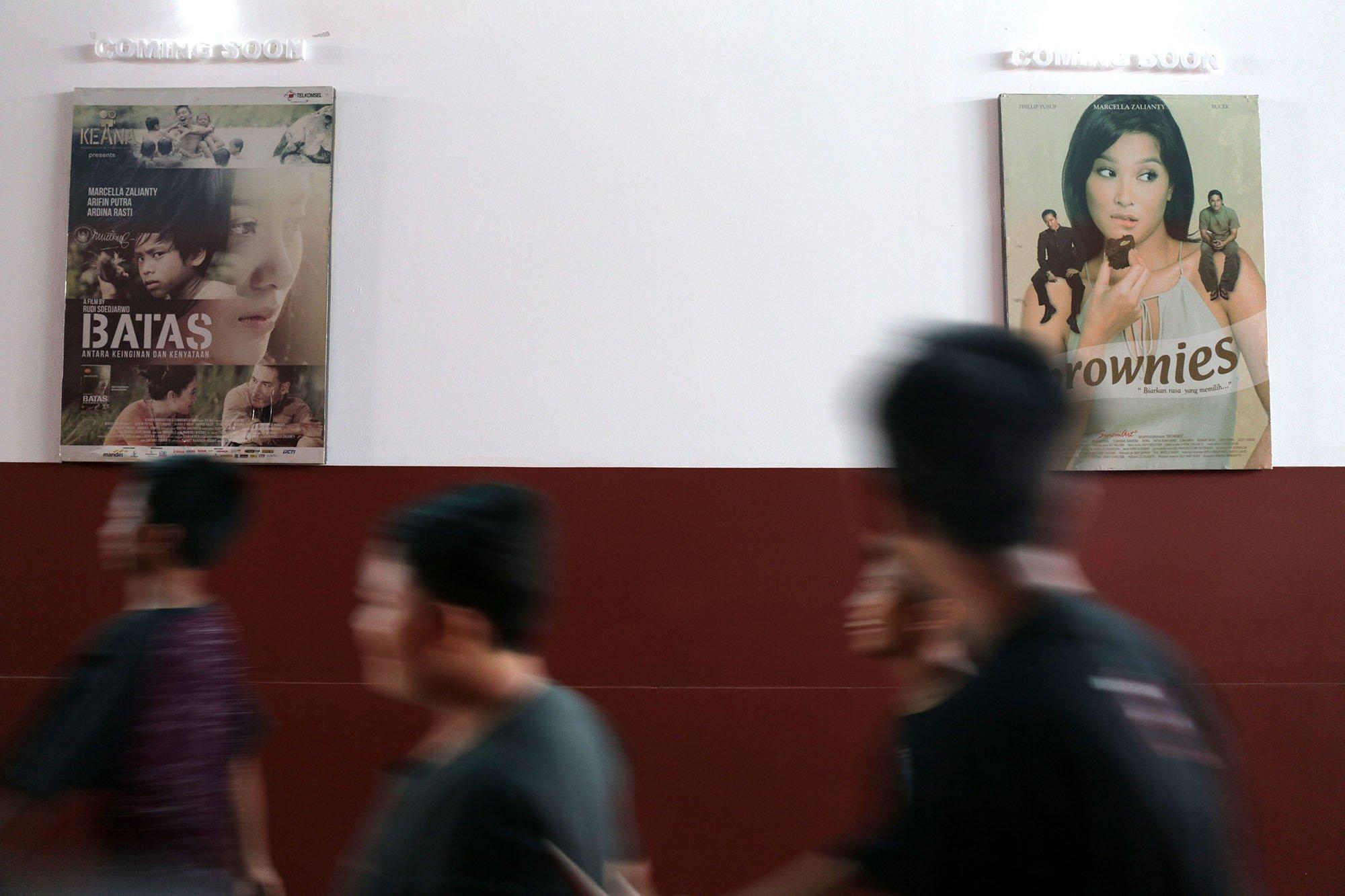 Sejumlah anak laki laki melintas didepan film yang diputar di Indiskop atau Bioskop Rakyat yang di dalam Pasar Jaya Teluk Gong, Penjaringan, Jakarta Utara, Selasa (2/7/2019). Bioskop rakyat yang khusus menayangkan film-film Indonesia ini memiliki 2 studio dengan kapasitas masing-masing 128 kursi penonton, 6 speaker, 1 proyektor layar, dan 3 pendingin ruangan. Dalam masa uji coba ini, warga yang ingin menjajal bioskop rakyat ini cukup merogoh kocek Rp. 15.000 untuk dewasa dan Rp. 5.000 untuk anak kecil.