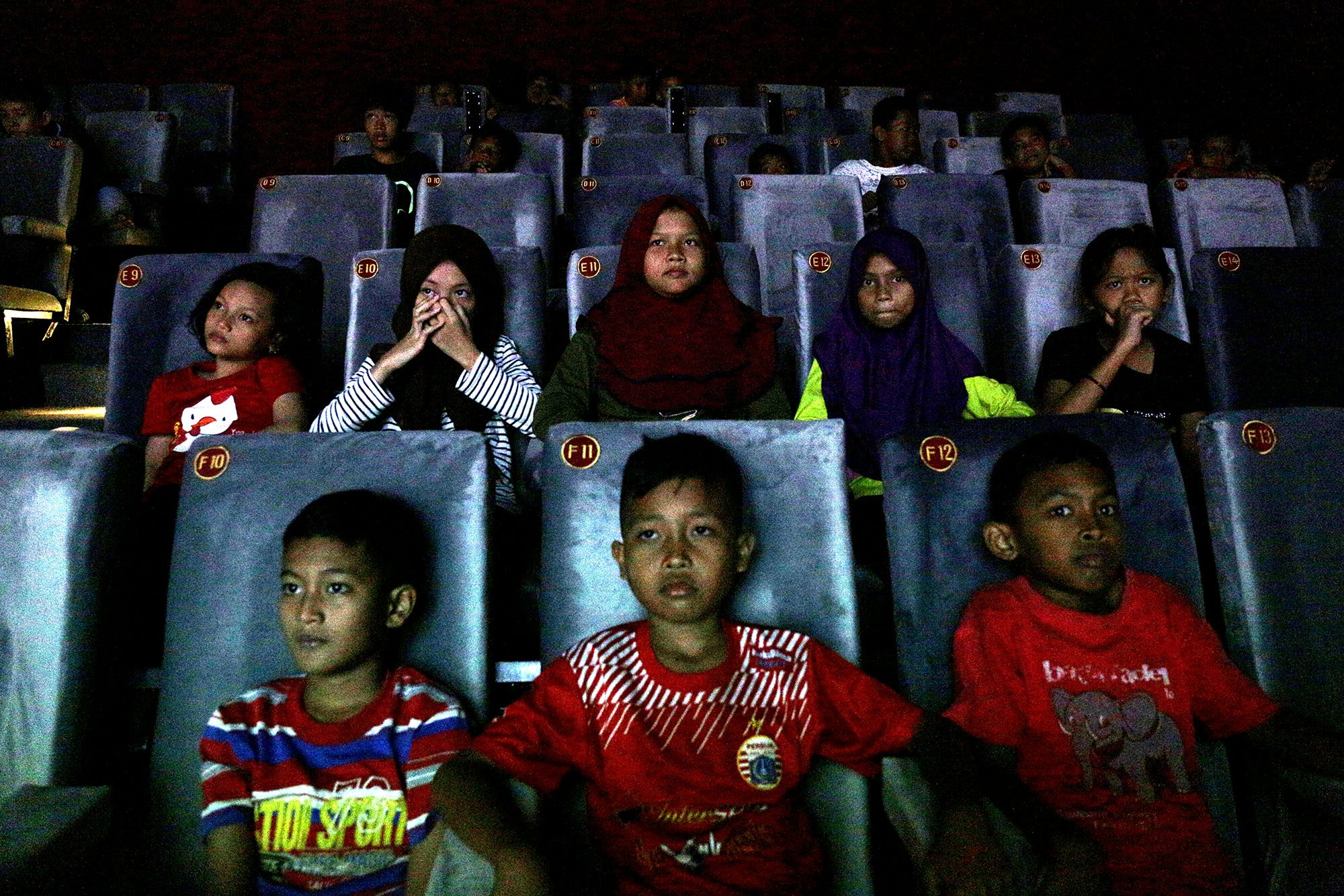 Sejumlah anak menonton film yang diputar di Indiskop atau Bioskop Rakyat yang di dalam Pasar Jaya Teluk Gong, Penjaringan, Jakarta Utara, Selasa (2/7/2019). Bioskop rakyat yang khusus menayangkan film-film Indonesia ini memiliki 2 studio dengan kapasitas masing-masing 128 kursi penonton, 6 speaker, 1 proyektor layar, dan 3 pendingin ruangan. Dalam masa uji coba ini, warga yang ingin menjajal bioskop rakyat ini cukup merogoh kocek Rp. 15.000 untuk dewasa dan Rp. 5.000 untuk anak kecil.