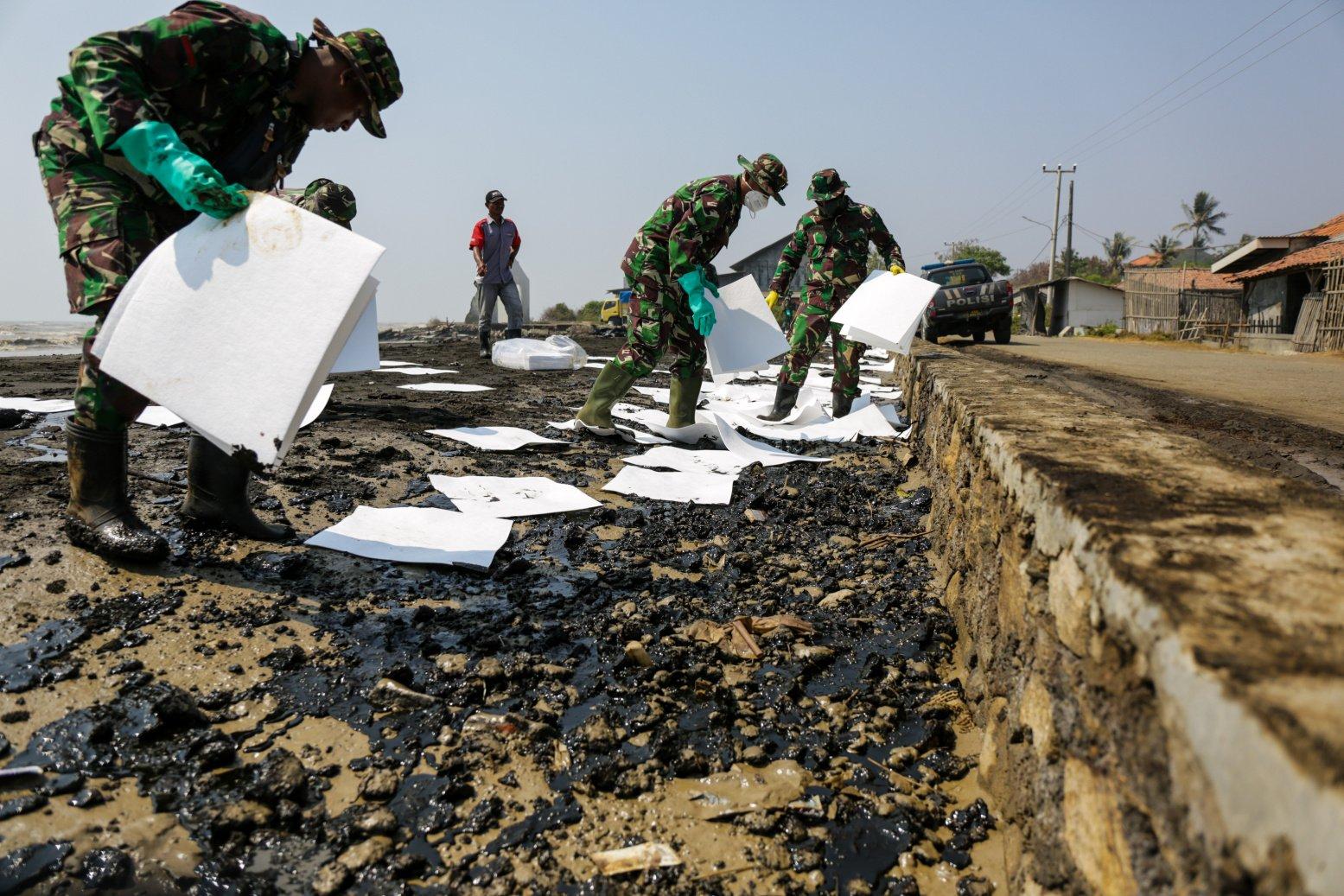 Warga dan tentara mengumpulkan tumpahan minyak milik Pertamina yang terserak di Pesisir Pantai Cemarajaya, Karawang, Jawa Barat, Jumat (24/7/2019).