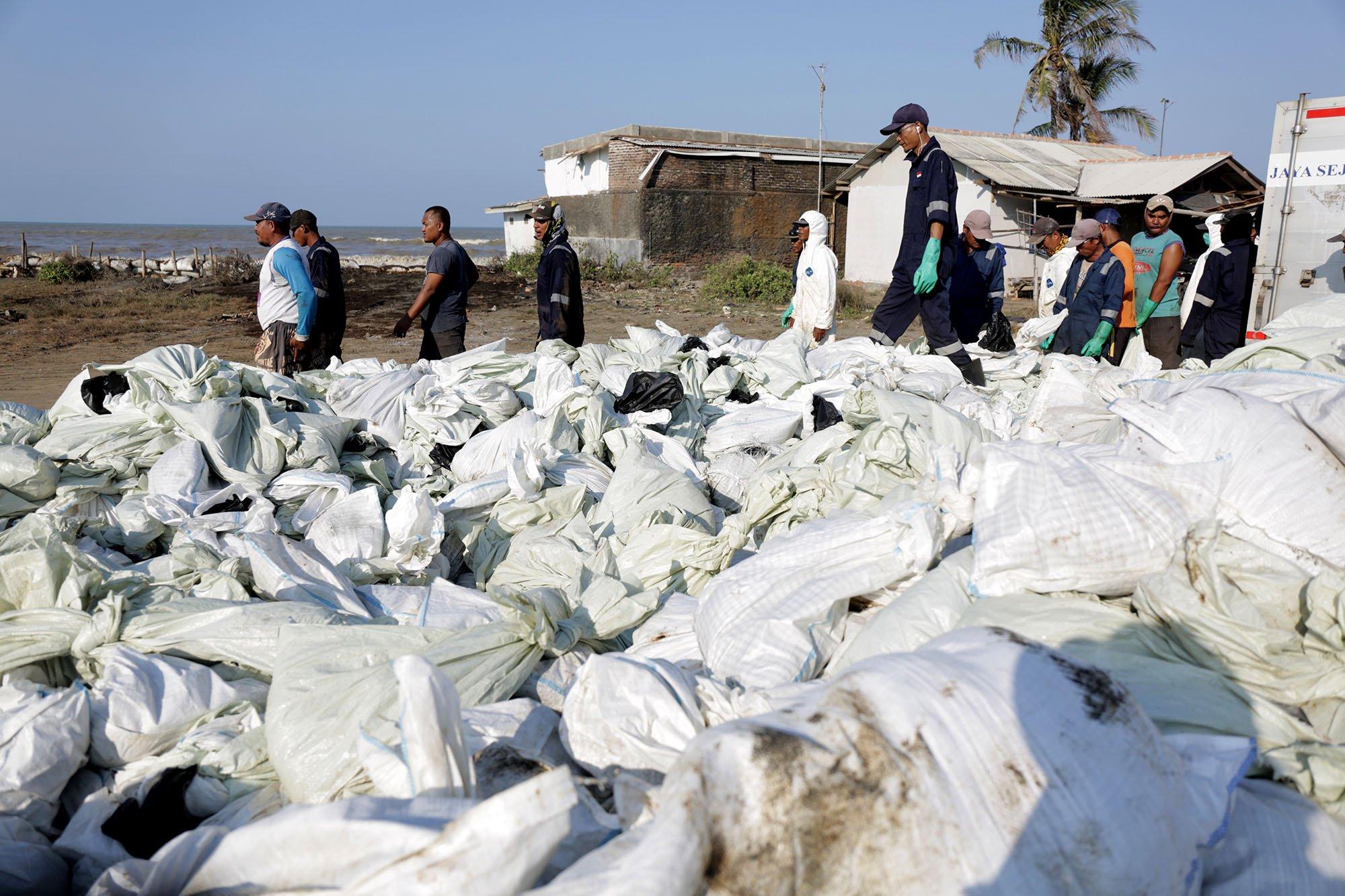 Para nelayan menaruh karung berisikan pasir yang tercampurkan oleh tumpahan minyak ONWJ, Cempaka Jaya, Karawang, Jawa Barat (19/8).