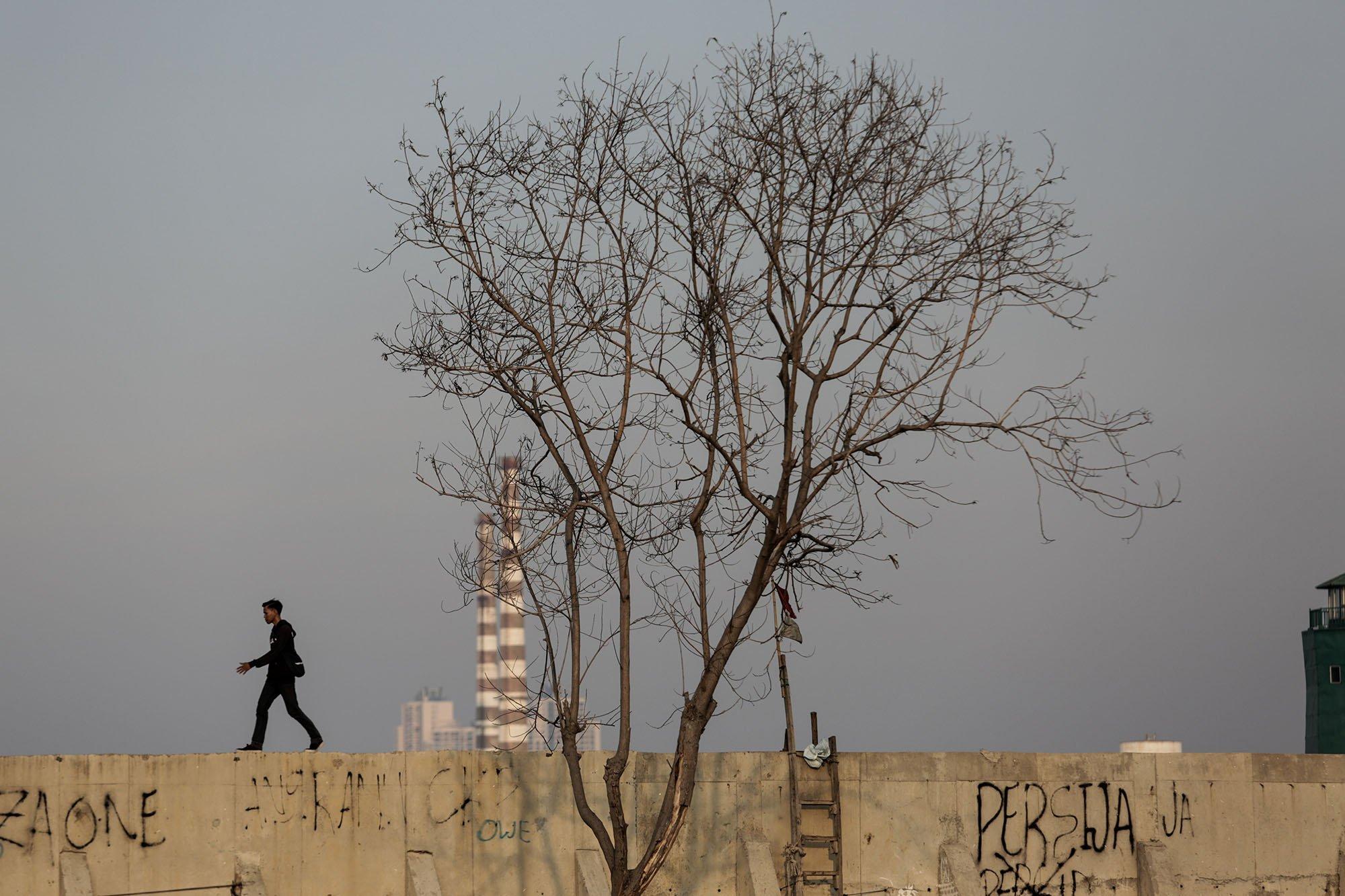 Seorang pria melintas di atas tanggul Pelindo II, Kampung Muara Baru, Penjaringan, Jakarta Utara, (11/9).