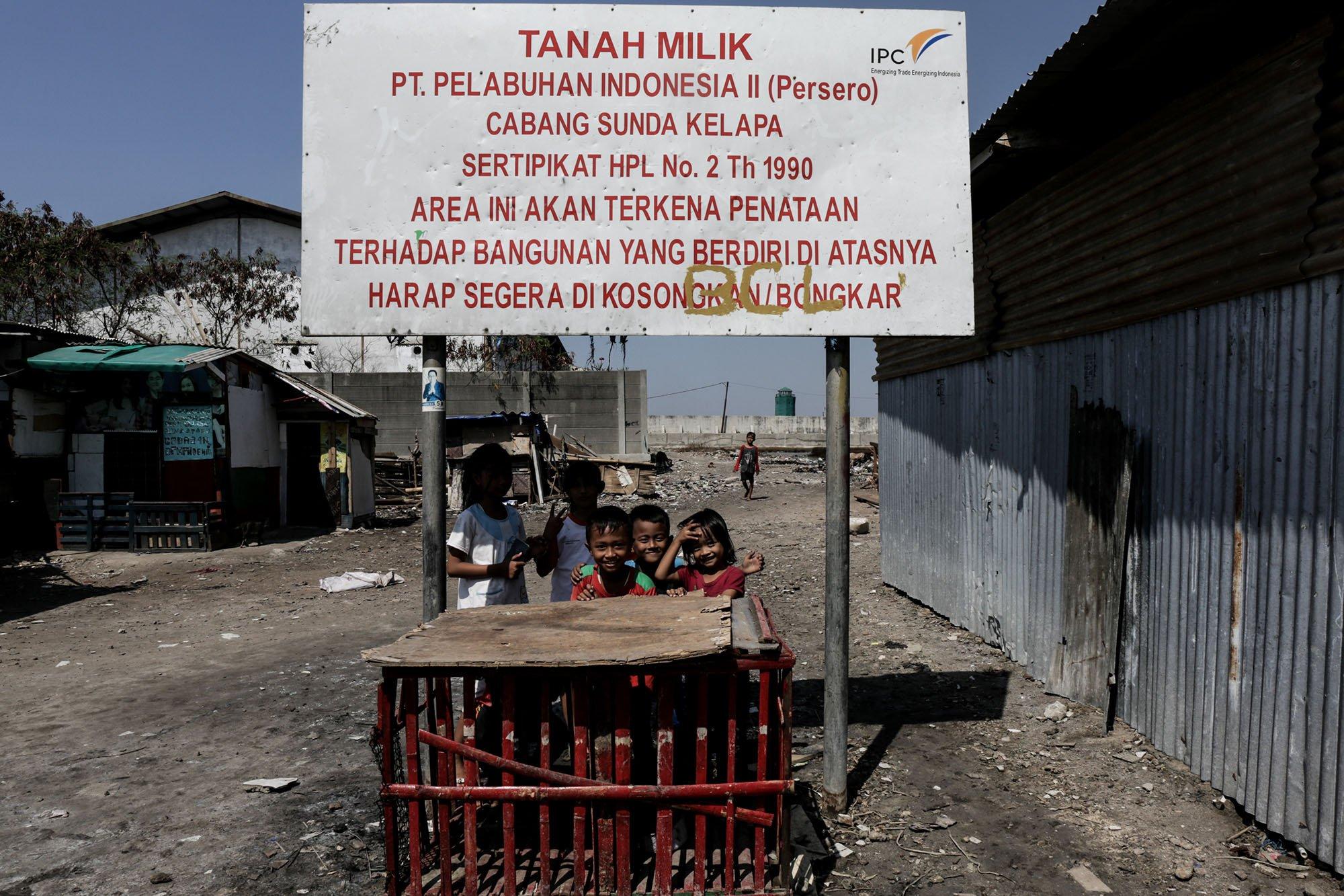 Sejumlah anak berdiri di bawah papan besi milik Pelindo II, Kampung Muara Baru, Jakarta Utara (11/9).