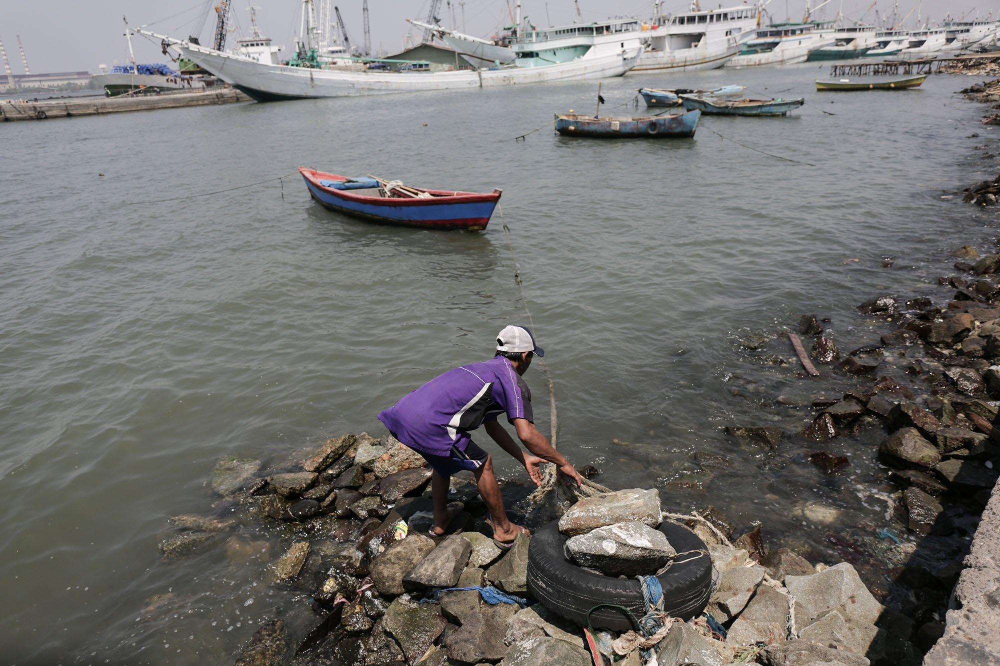 Wahyu (48) menarik kapalnya di Pantai Muara Baru, Jakarta Utara (11/9).