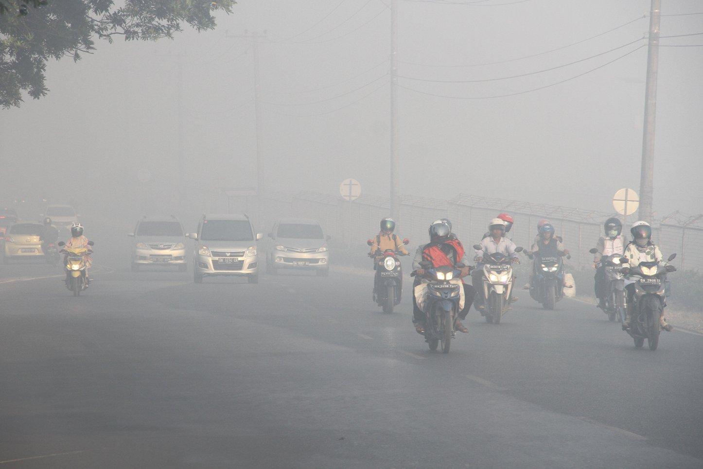 Sejumlah kendaraan bermotor melintas di jalan Ahmad Yani yang di selimuti kabut asap pekat di Landasan Ulin, Banjarbaru, Kalimantan Selatan, Rabu (11/9/2019). Kebakaran hutan dan lahan di sejumlah daerah Kalsel menimbulkan kabut asap yang menggangu aktivitas warga.