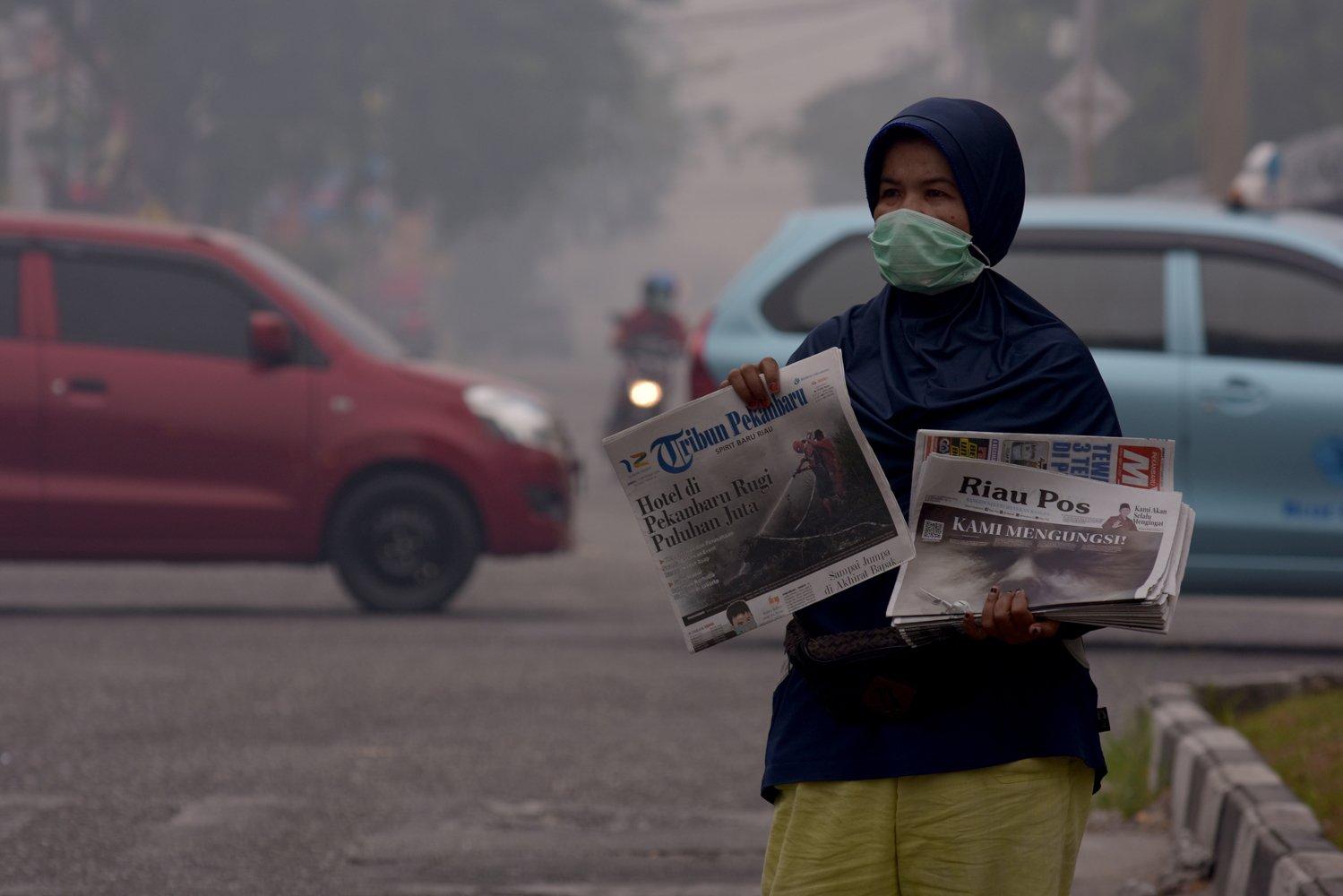 Seorang penjual koran mengenakan masker medis saat berjualan di tengah asap kebakaran hutan dan lahan (Karhutla) yang makin pekat menyelimuti Kota Pekanbaru, Riau, Jumat (13/9/2019). Pusat Pengendalian Pembangunan Ekoregion (P3E) Sumatera hasil pengukuran Indeks Standar Pencemar Udara (ISPU) menunjukan sebagian besar daerah di Riau dalam kualitas udara dalam kategori berbahaya karena tercemar asap Karhutla.