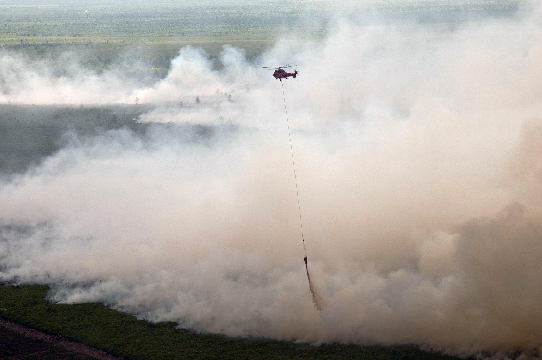 Helikopter Superpuma APP-Sinar Mas membantu membantu pemadaman kebakaran lahan gambut di Kecamatan Tanah Putih Kabupaten Rokan Hilir, Riau, Kamis (23/2). Upaya pemadaman kebakaran di pesisir Riau terus berkobar menghanguskan sekitar 100 hektare lahan, yang diduga dipicu oleh pembukaan lahan dengan membakar untuk perkebunan kelapa sawit.