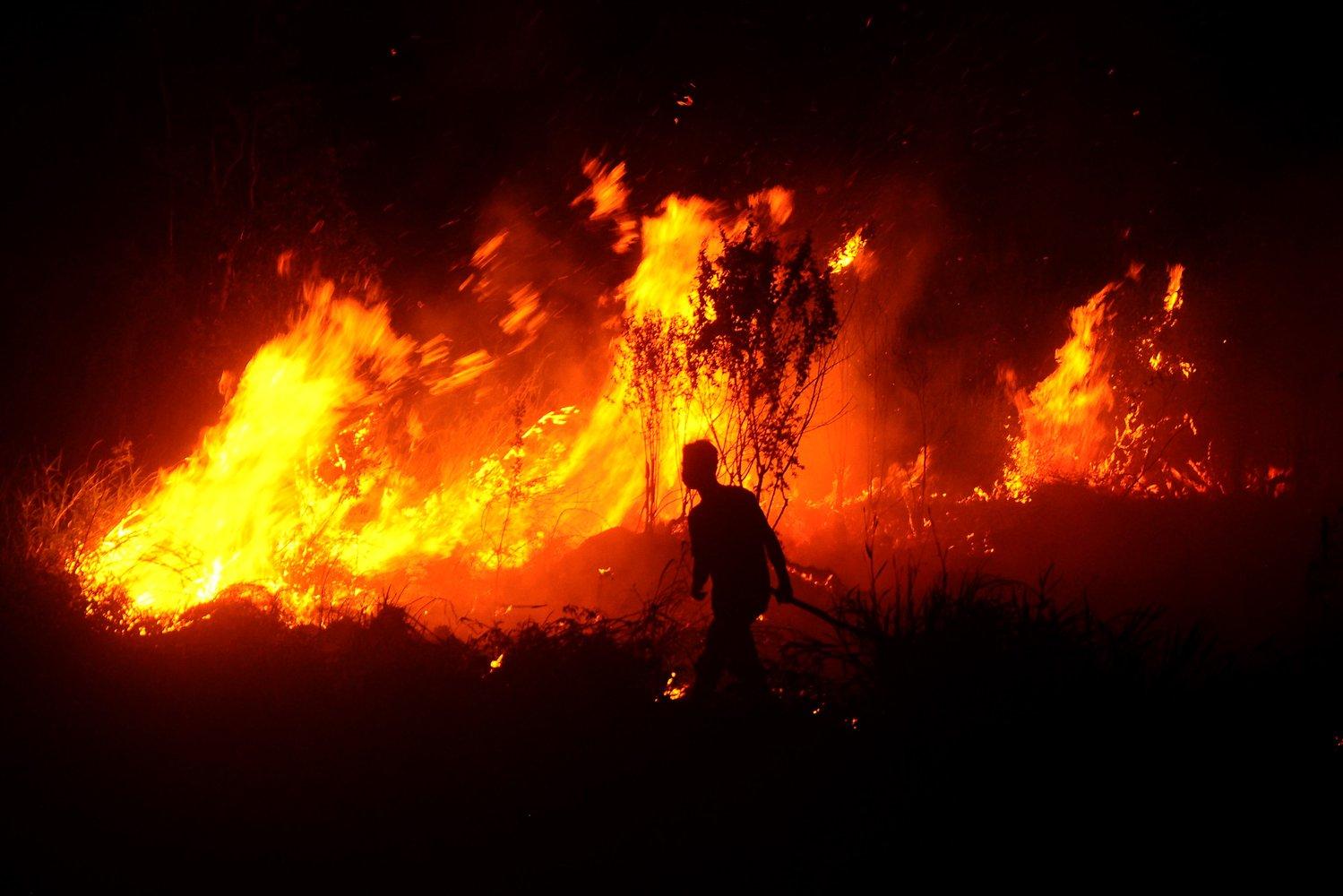 Warga berupaya memadamkan kebakaran lahan gambut di desa Pulau Semambu, Ogan Ilir, Sumatera Selatan, Selasa (6/8/2019).