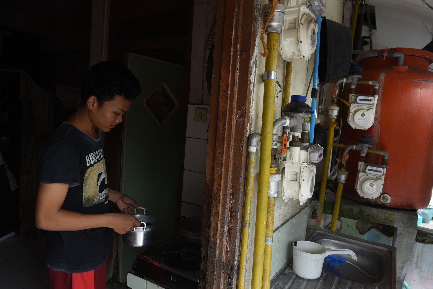 Seorang warga memasak menggunakan gas PGN di salah satu rumah susun di Surabaya, Jawa Timur.
