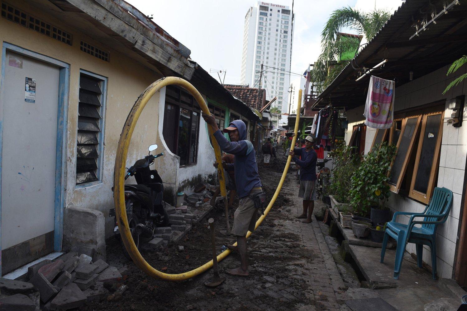 Pekerja menyelesaikan pemasangan pipa gas PGN di sebuah permukiman di Surabaya, Jawa Timur.