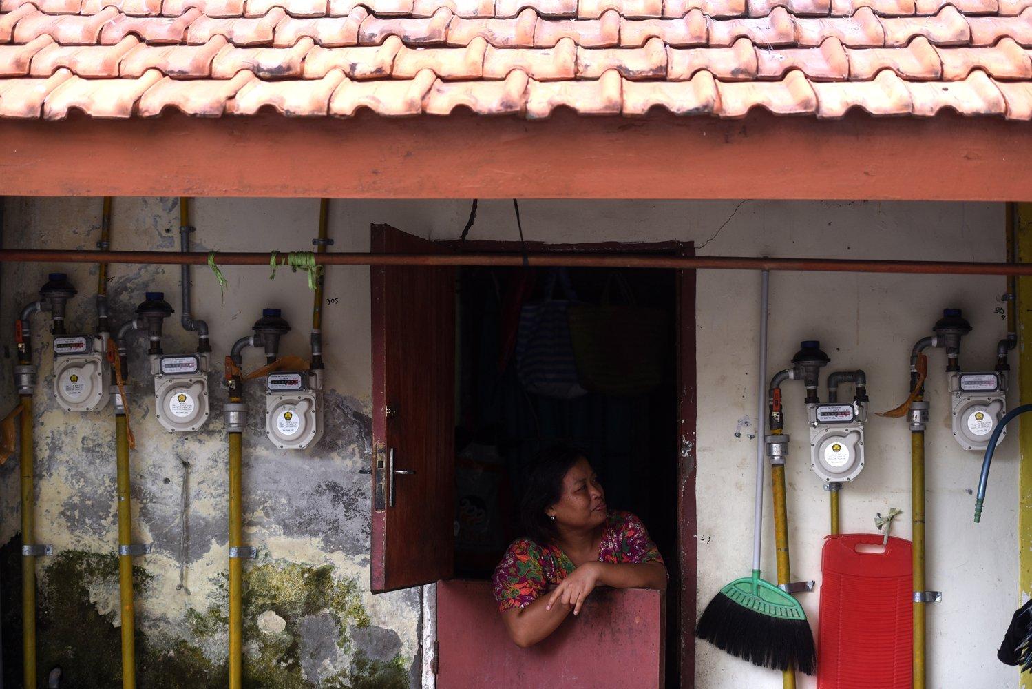 Seorang ibu mengamati meteran gas yang terpasang di dinding rumahnya di salah satu rumah susun di Surabaya, Jawa Timur.