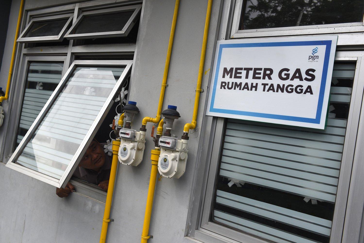 Seorang warga mengamati meteran gas yang terpasang di dinding rumahnya di salah satu rumah susun di Surabaya, Jawa Timur.