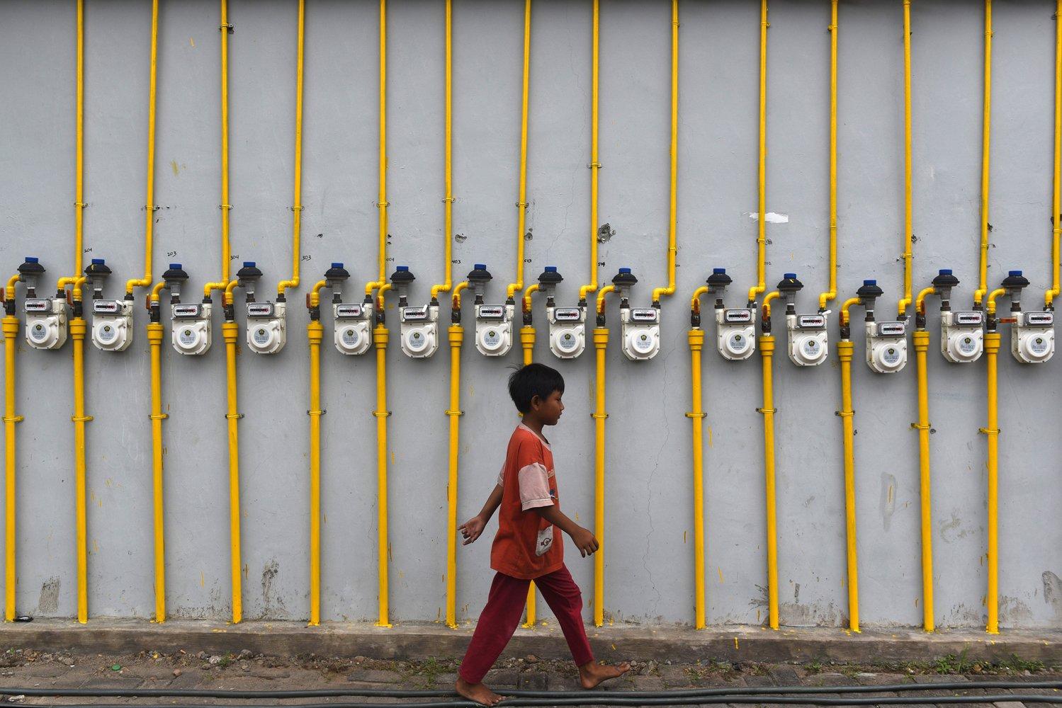 Seorang melintas di depan meteran gas yang terpasang di dinding rumah susun di Surabaya, Jawa Timur.