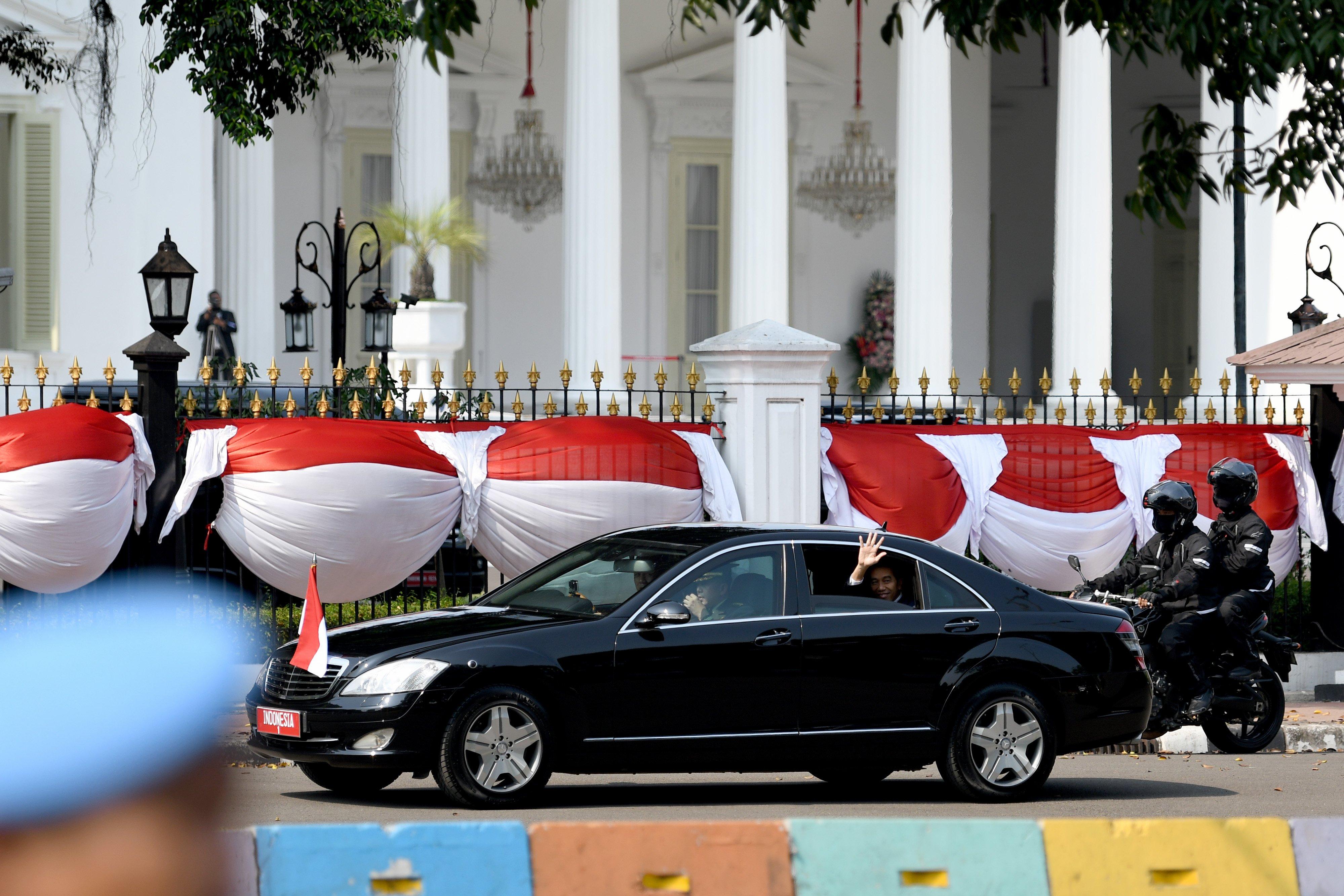 Presiden Joko Widodo melambaikan tangan kepada warga dari dalam mobil saat menuju lokasi upacara pelantikan Presiden dan Wakil Presiden periode 2019-2024 di Jakarta, Minggu (20/10/2019).